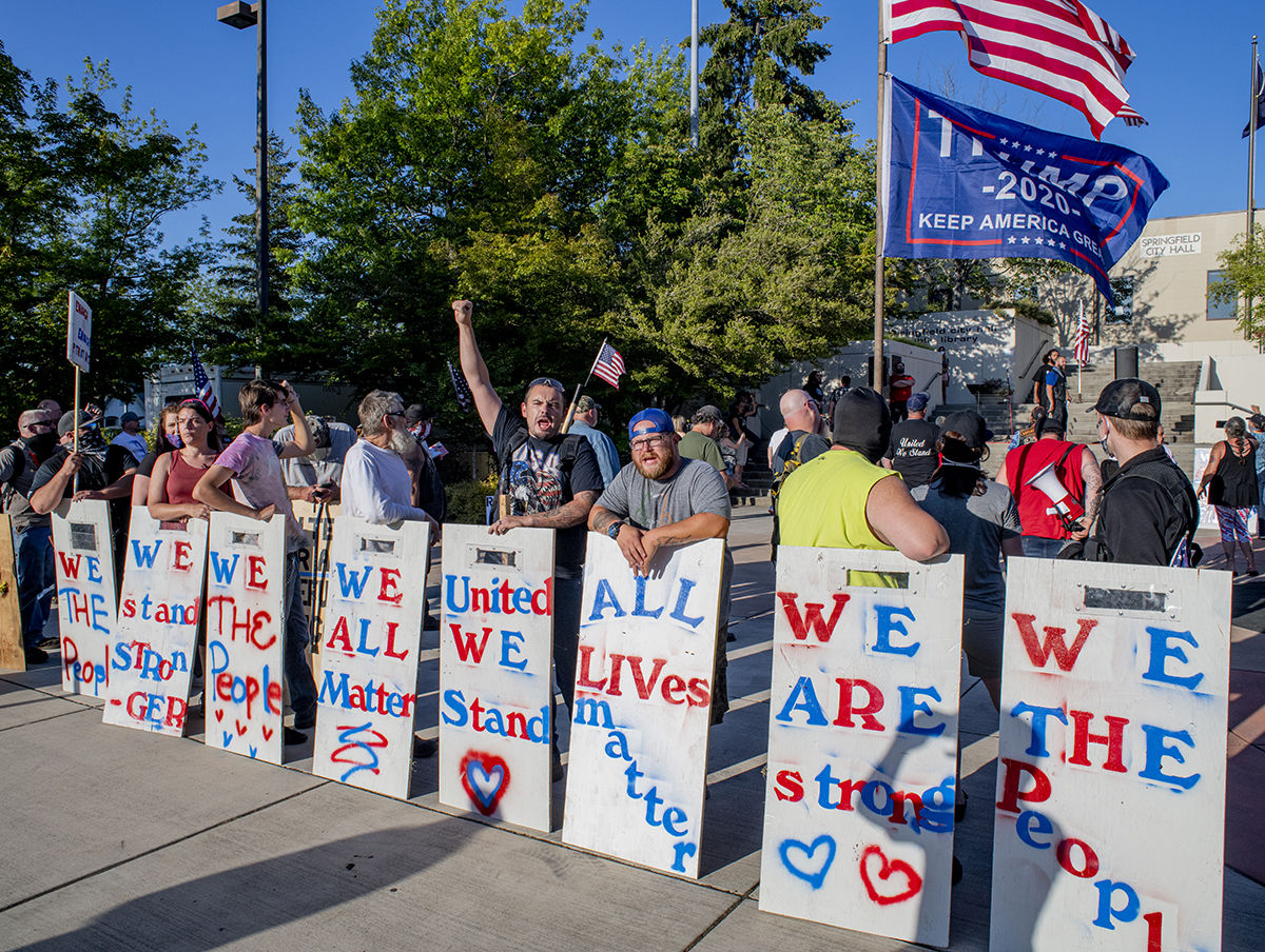 About 250 people gathered at the Springfield, Oregon, library for what was billed as an All Lives Matter rally Friday at 7 p.m. About a dozen counter protesters also attended. The signs the particpants stand behind are made of plywood and serve as shields in a physical confrontation. The event was mostly peaceful, although a couple of minor scuffles broke out and one man was taken into custody by the Springfield police. By 9:30 p.m. both the protesters and the counter protesters dispersed. Photo by Dan Morrison