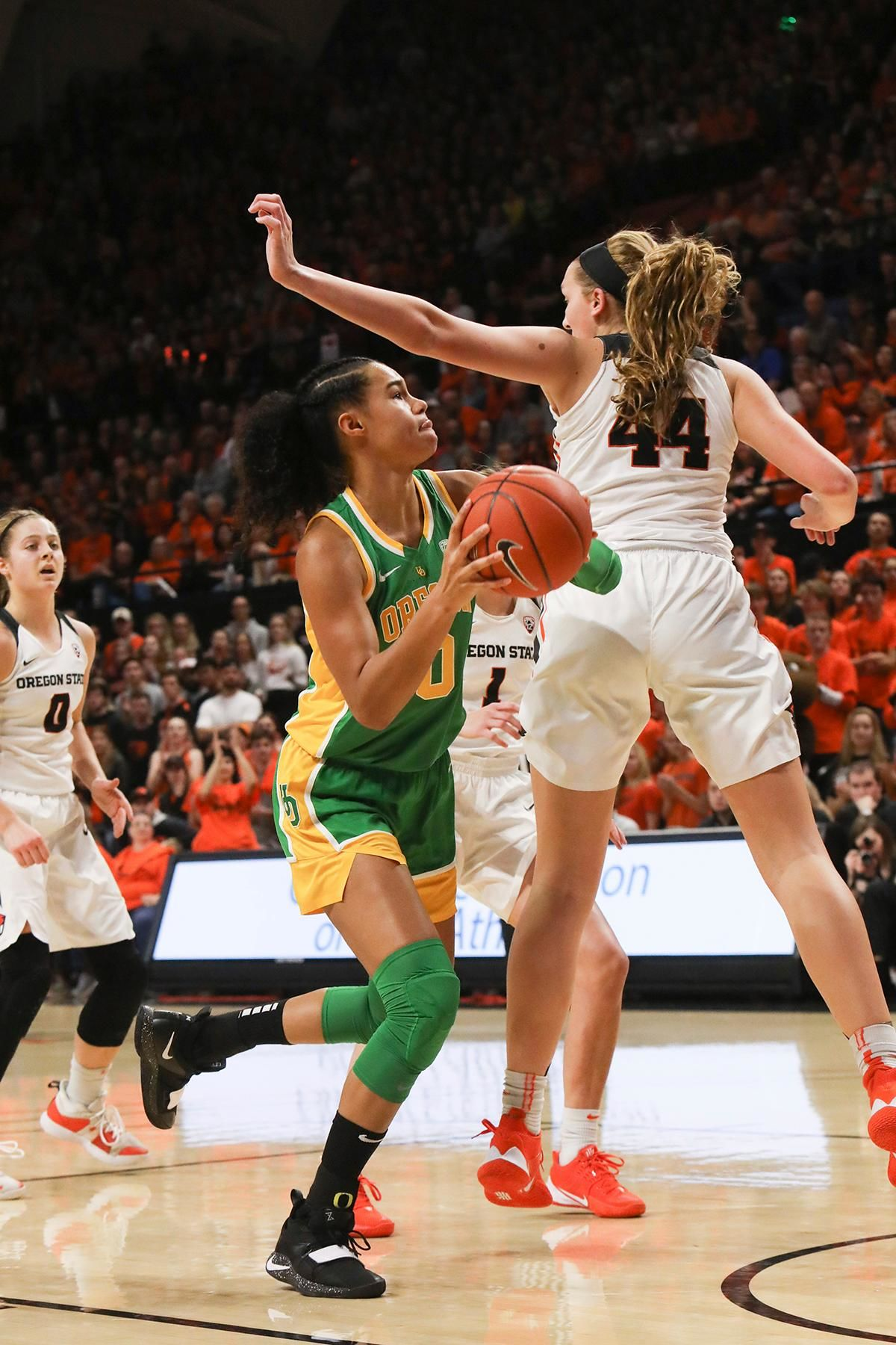 Oregon's Satou Sabally (0) darts behind Oregon State's Taylor Jones (44) to shoot to the basket during the first half of an NCAA college basketball game in Corvallis, Ore., Sunday, Jan. 26, 2020. (AP Photo/Amanda Loman)