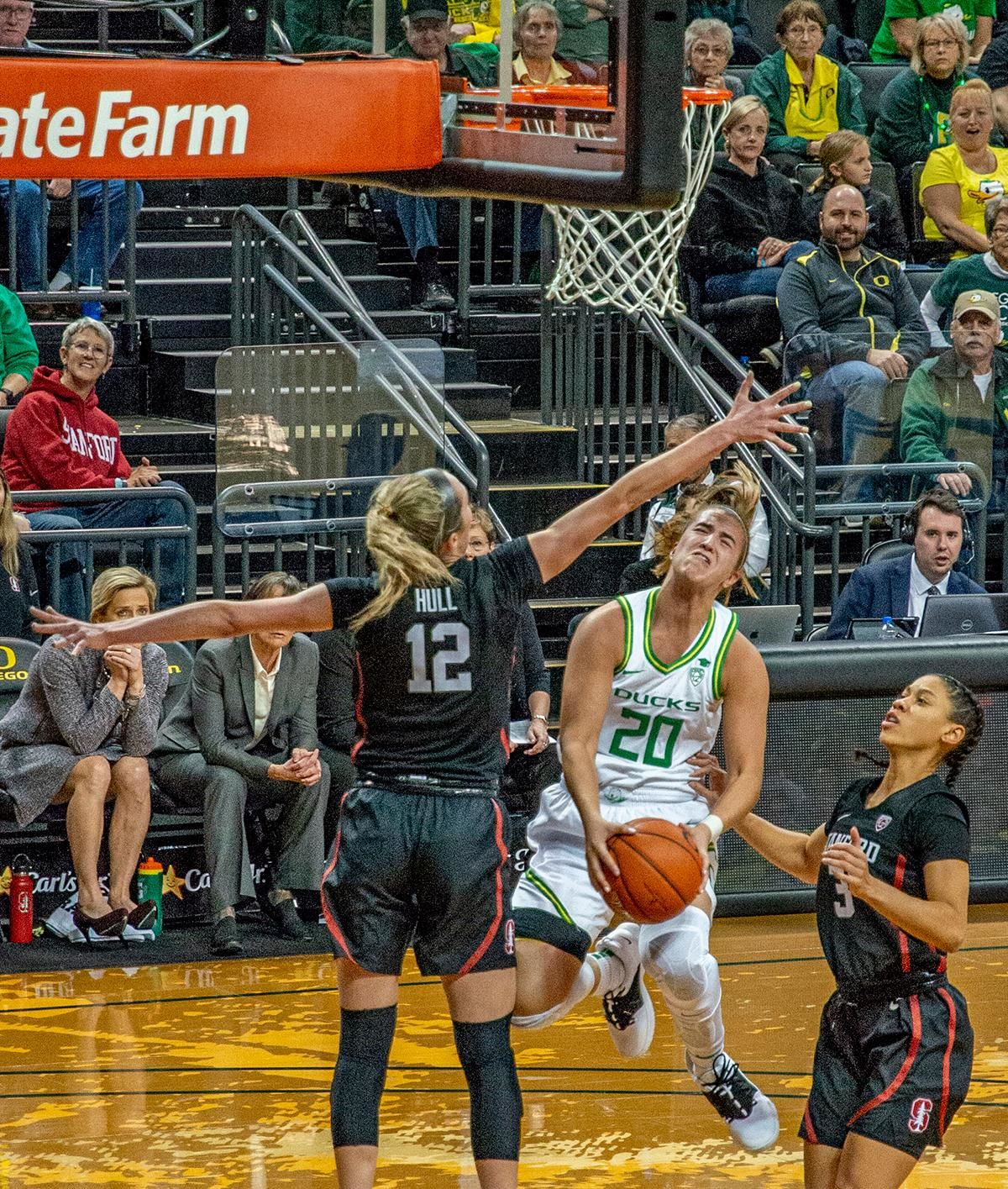 Oregon's point guard Sabrina Ionescu, #20, goes up and under over Stanford's forward Lexie Hull, #12, for a reverse layup. The #6 University of Oregon Ducks women's basketball team defeated #3 Stanford Cardinal 87-55 in front of a sold out crowd of 12, 218 fans in Matthew Knight Arena. Sabrina Ionescu broke the all-time Oregon scoring record of 2,253 and ended the game with 37 points, 11 rebounds, another double-double. Satou Sabally added 18 points and 11 rebounds, also a double-double. Ruthy Hebard put up 11 points with 5 rebounds, and Minyon Moore added 10 points 3 rebounds. The Ducks next face off against Cal on Sunday, January 19, at 2 pm in Matthew Knight Arena. Photo by Jeffrey Price