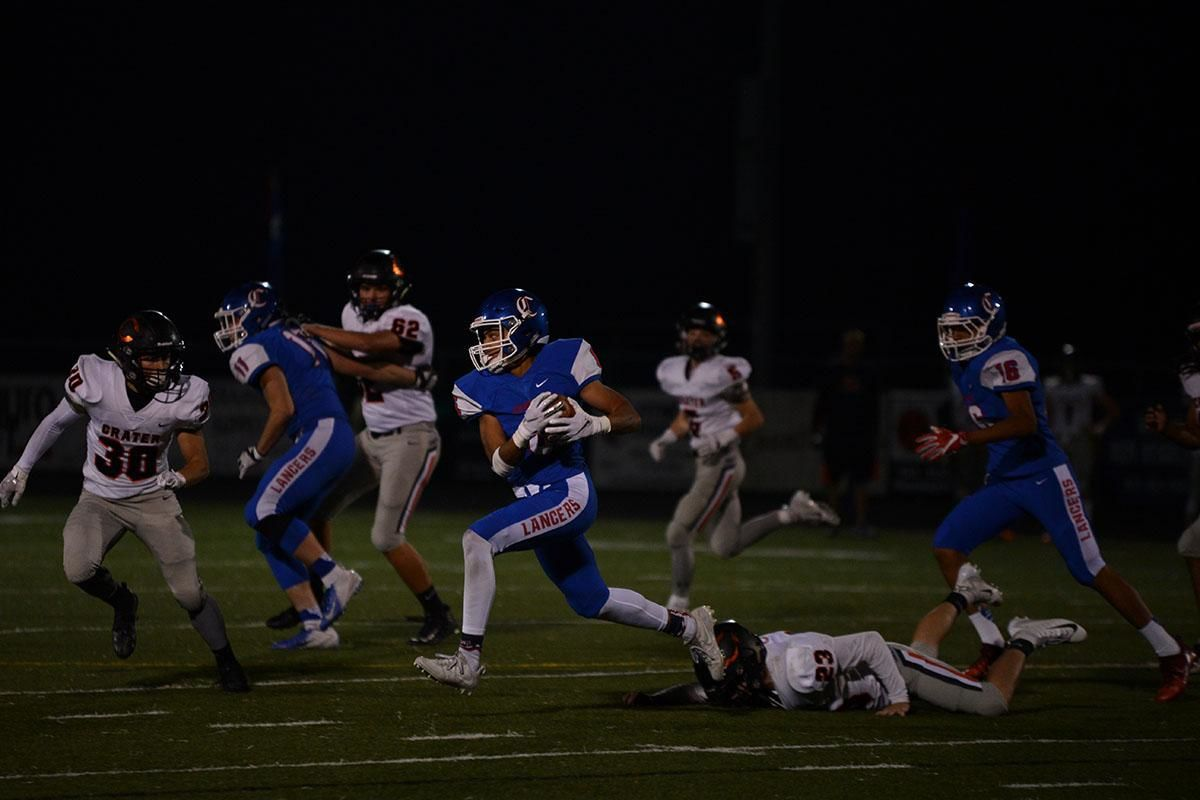 Churchill wide receiver Elijah Fields (6) piles up yardage against Crater. The Churchill Lancers dominated the Crater Comets 58-20 in front of a packed Homecoming crowd. With the win Churchill advances to the 5A district playoffs. Photo by Emilee Jackson