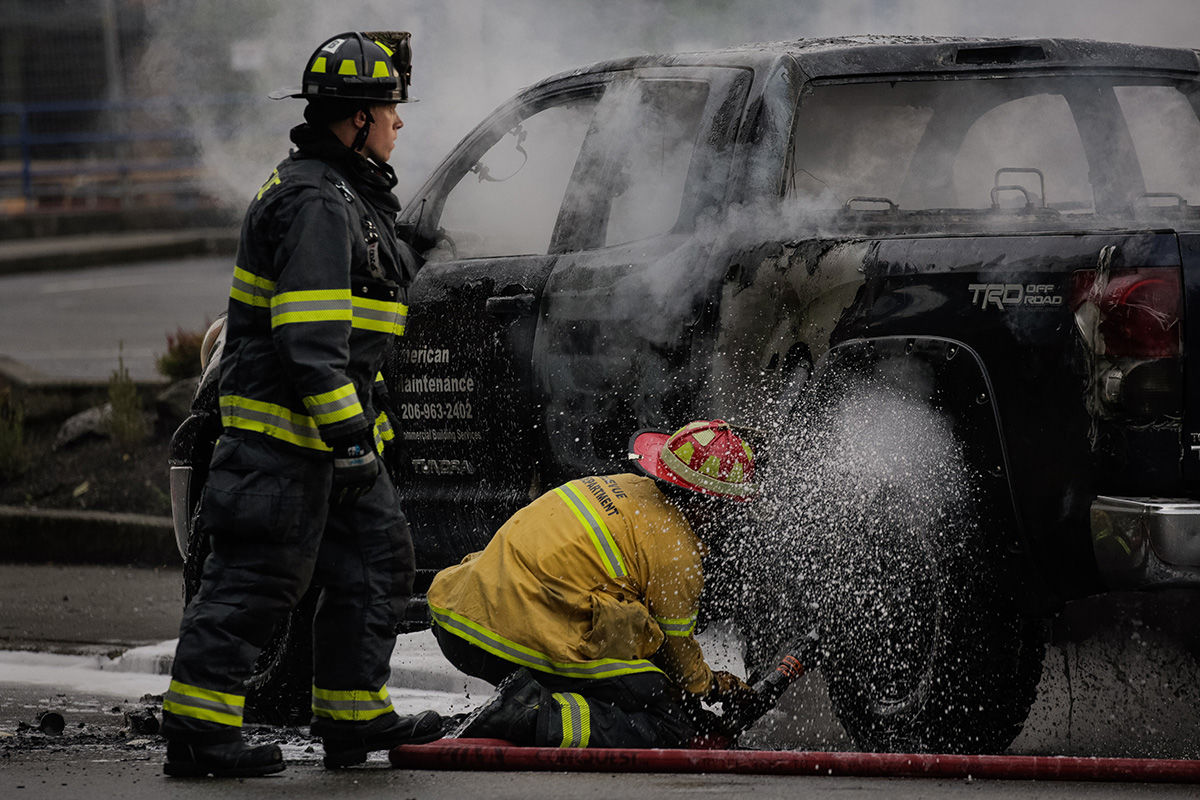 BELLEVUE, WA - MAY 31: Firefighters extinguish a truck fire on May 31, 2020 in Bellevue, Washington. Protests due to the recent death of George Floyd took place in Bellevue in addition to Seattle, with looting in Bellevue and at least one burned automobile there. (Photo by David Ryder/Getty Images)