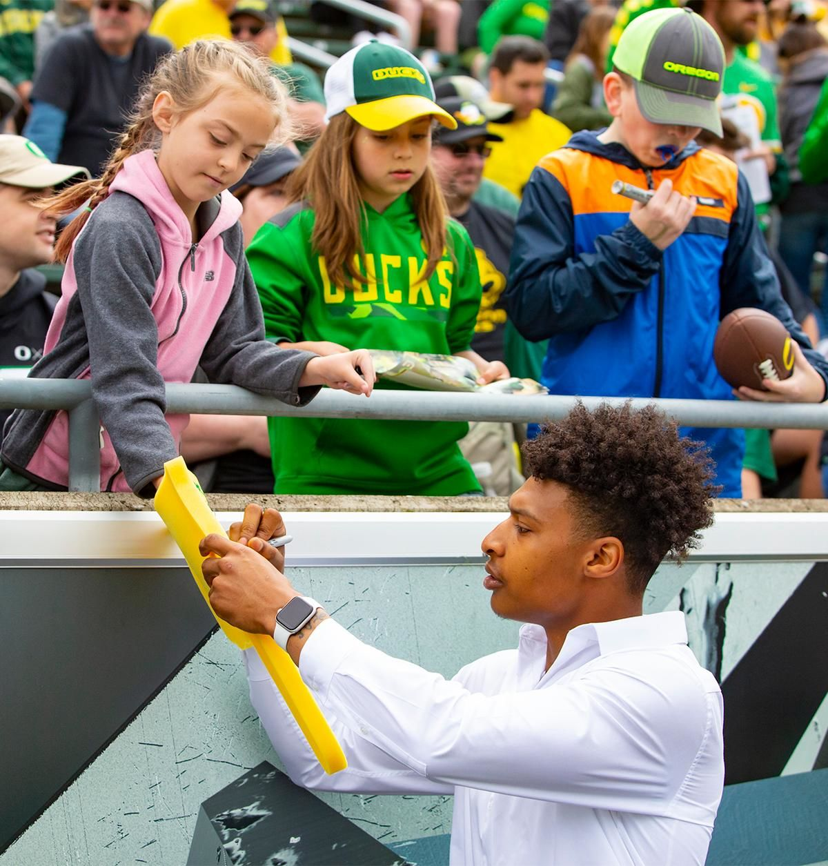 Former Oregon basketball star Dillon Mitchell signs a fan's foam finger during the game. More than 35,000 fans turned out for the University of Oregon's annual spring football game. Mighty Oregon defeated the Fighting Ducks 20 to 13 during the Saturday afternoon game at Autzen Stadium in Eugene, Ore. on April 20, 2019. [Ben Lonergan for KVAL.com] - KVAL.com