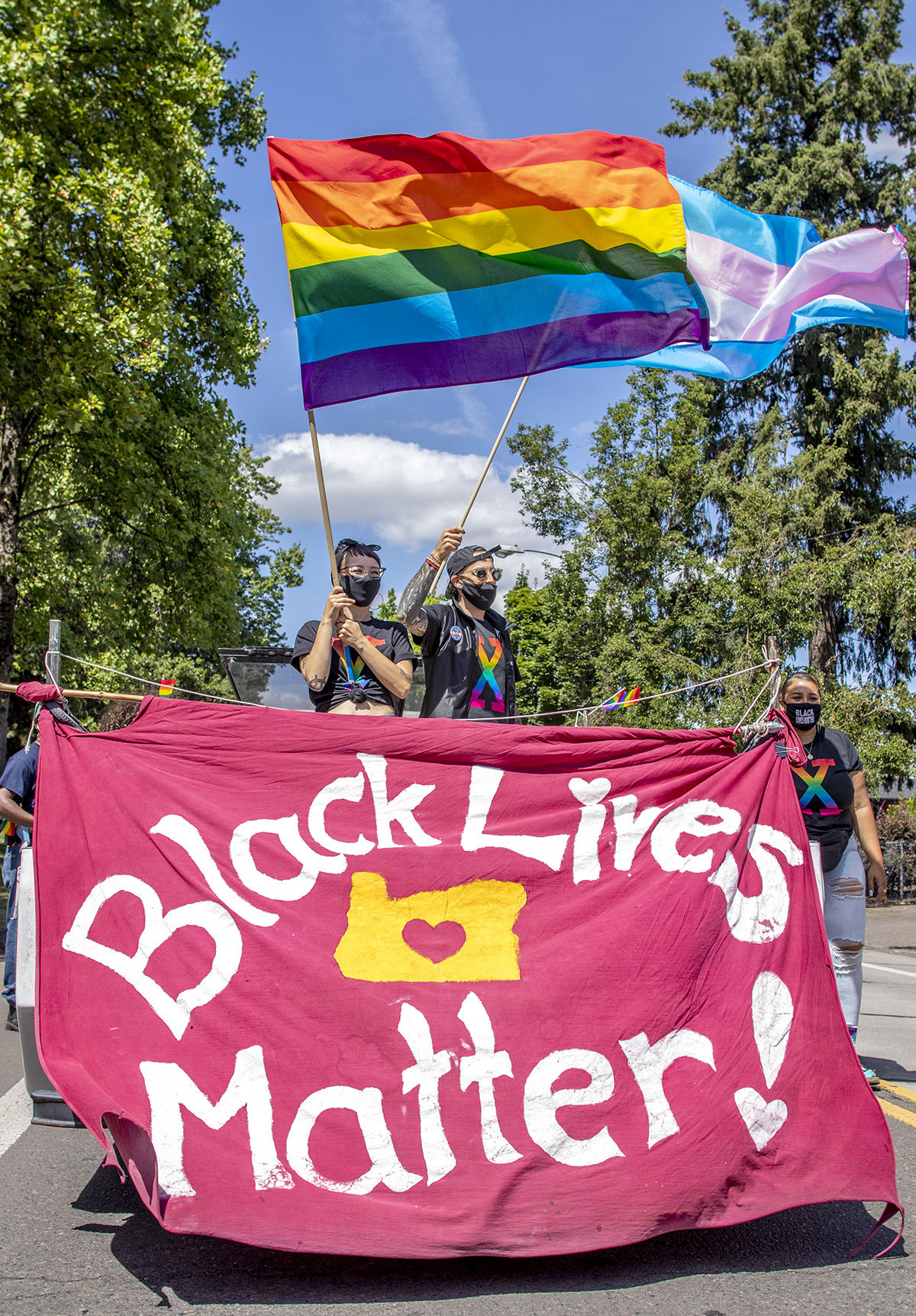 Demonstrators holding flags in the back of a pickup truck leading the march. Approximately 200 people gathered in front of the federal courthouse at noon in Eugene, Oregon, on Saturday to celebrate and march for Black Trans Lives. The march, organized by local groups Black Unity and Eugene Pride, made its way through the streets of Eugene until arriving at Kiwanis/Skinner Butte Park. Once at the park marchers stopped to enjoy food, music and demonstrations held by the march organizers. Photo by Payton Bruni