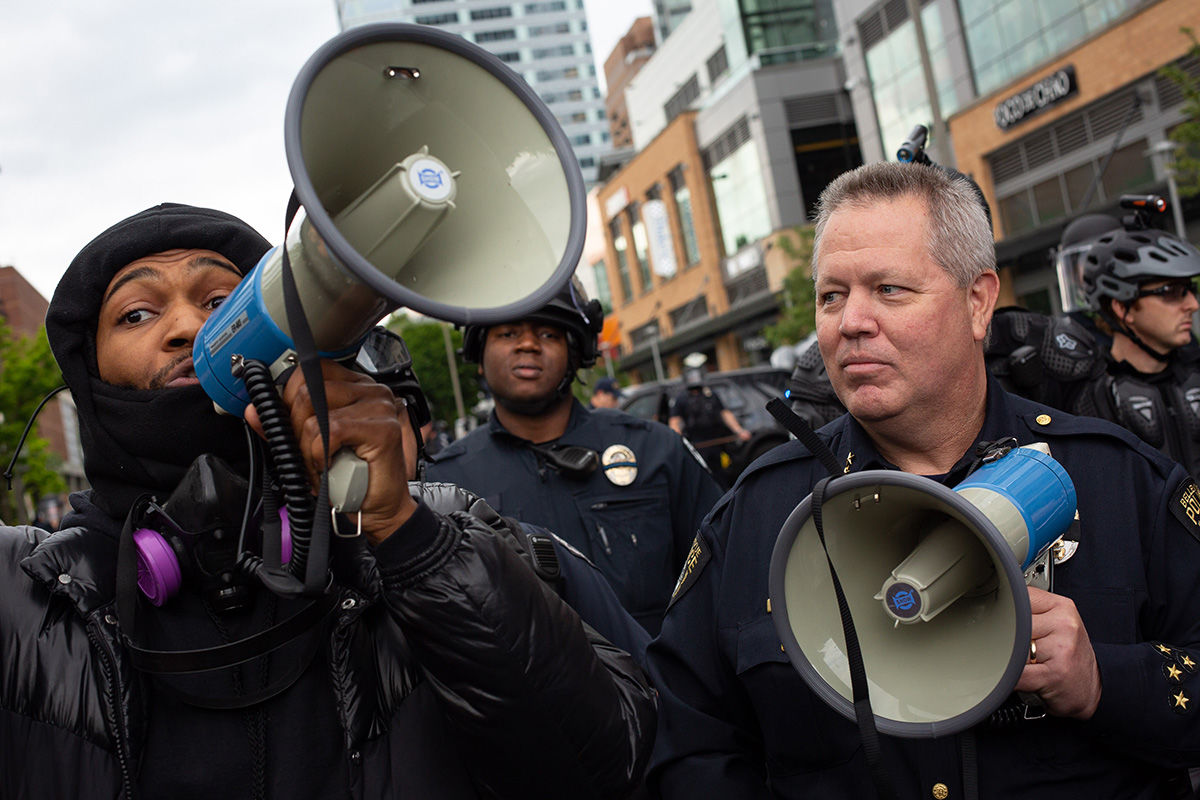 BELLEVUE, WA - MAY 31: A demonstrator wields a megaphone next to Bellevue Police Chief Steve Mylett as they converse during a gathering to protest the recent death of George Floyd on May 31, 2020 in Bellevue, Washington. Protests due to the recent death of George Floyd took place in Bellevue in addition to Seattle, with looting in Bellevue and at least one burned automobile there. (Photo by David Ryder/Getty Images)