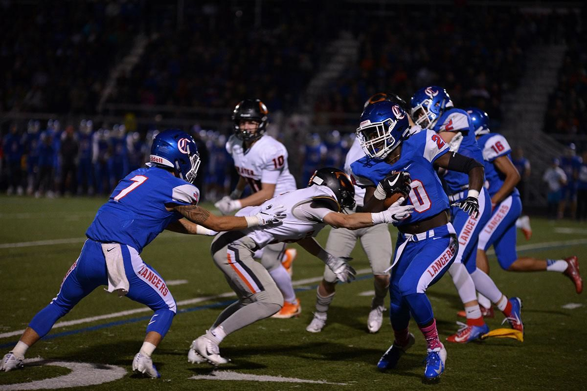 Churchill running back Deonte Jones (20) attempts to shake off the Crater defense. The Churchill Lancers dominated the Crater Comets 58-20 in front of a packed Homecoming crowd. With the win Churchill advances to the 5A district playoffs. Photo by Emilee Jackson