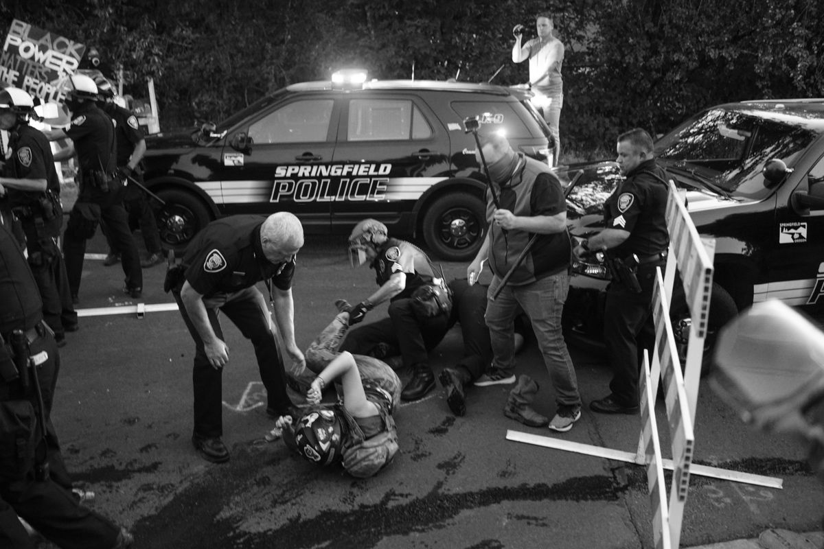 A female protester is dragged into police custody. Approximately 150 Black Unity protesters marched through the Thurston neighborhood in Springfield Wednesday evening. At about 9 p.m. the protesters arrived at a Springfield police-manned roadblock. After about a 30-minute standoff, the protesters began to push against the barriers, which led to a physical confrontation and arrests. Photo by Robert Scherle