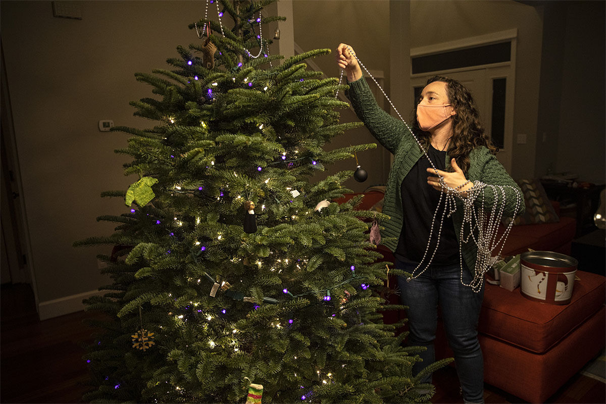 Ani Sirois puts lights and decorations on the family's Christmas tree at her home on Tuesday, Nov.  24, 2020 in Portland, Ore. (AP Photo/Paula Bronstein)