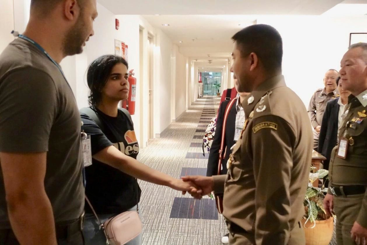 In this photo released by the Immigration Police,  Saudi woman Rahaf Mohammed Alqunun, second left, shakes hand with Chief of Immigration Police Maj. Gen. Surachate Hakparn before leaving the Suvarnabhumi Airport in Bangkok. (Immigration police via AP)