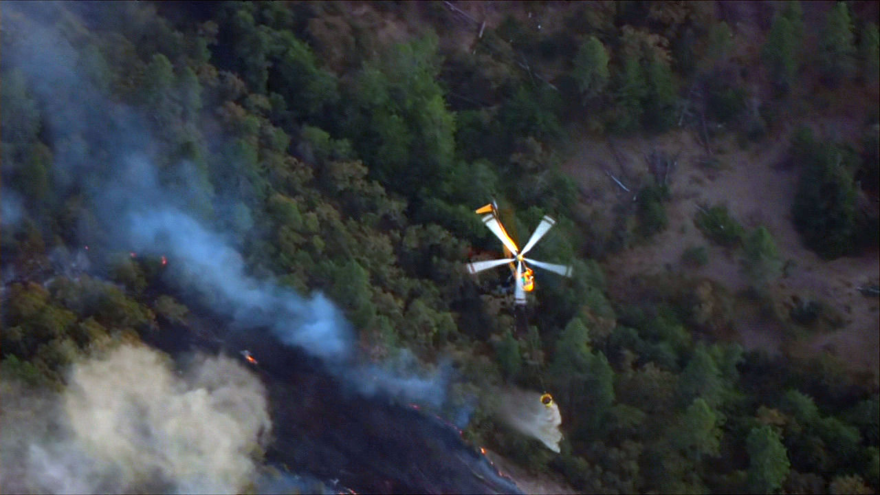 A helicopter dumps water on the Mosier Creek Fire in the Columbia River Gorge Wednesday night, Aug. 12, 2020. (KATU/Chopper 2)