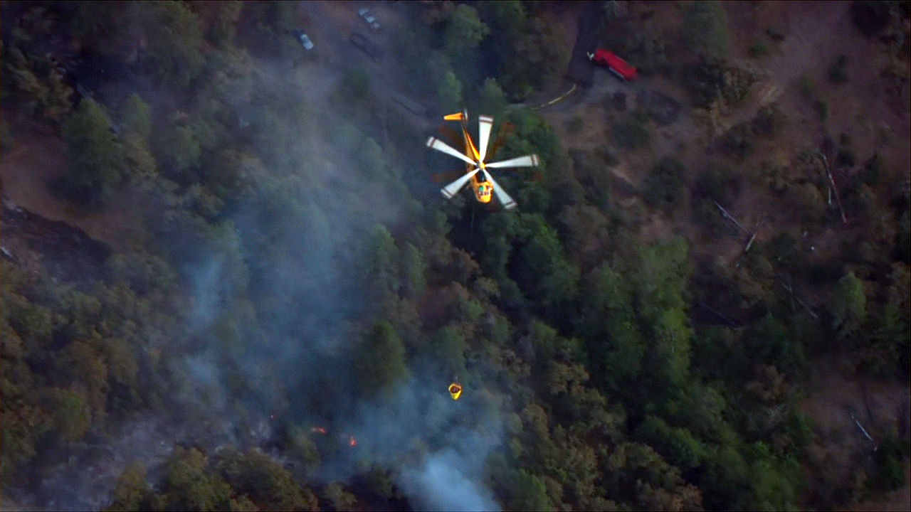A helicopter prepares to dump water on the Mosier Creek Fire in the Columbia River Gorge Wednesday night, Aug. 12, 2020. (KATU/Chopper 2)