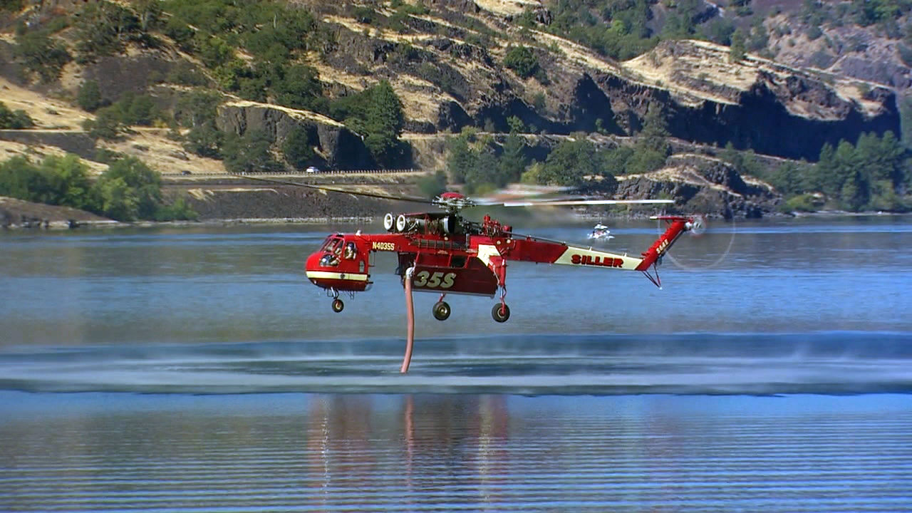 A helicopter dips into the Columbia River Friday, Aug. 14, 2020 to fill up with water in the battle against the Mosier Creek Fire. The fire has burned nearly 1,000 acres and destroyed at least four structures. (KATU)