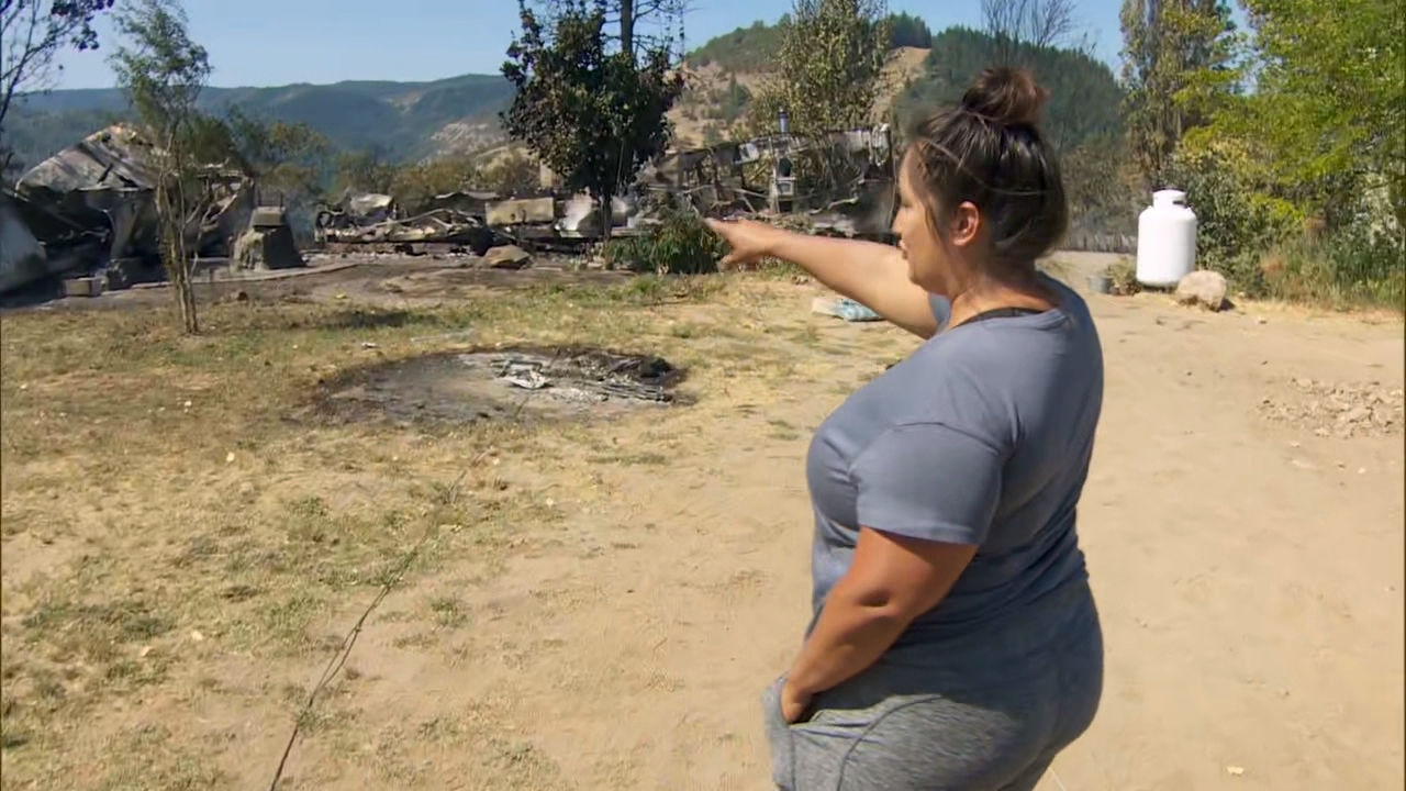 July Maus points to her property Thursday, Aug. 13, 2020 destroyed by the Mosier Creek Fire in the Columbia River Gorge. The fire had burned 800 acres and forced 900 people to evacuate. (KATU)
