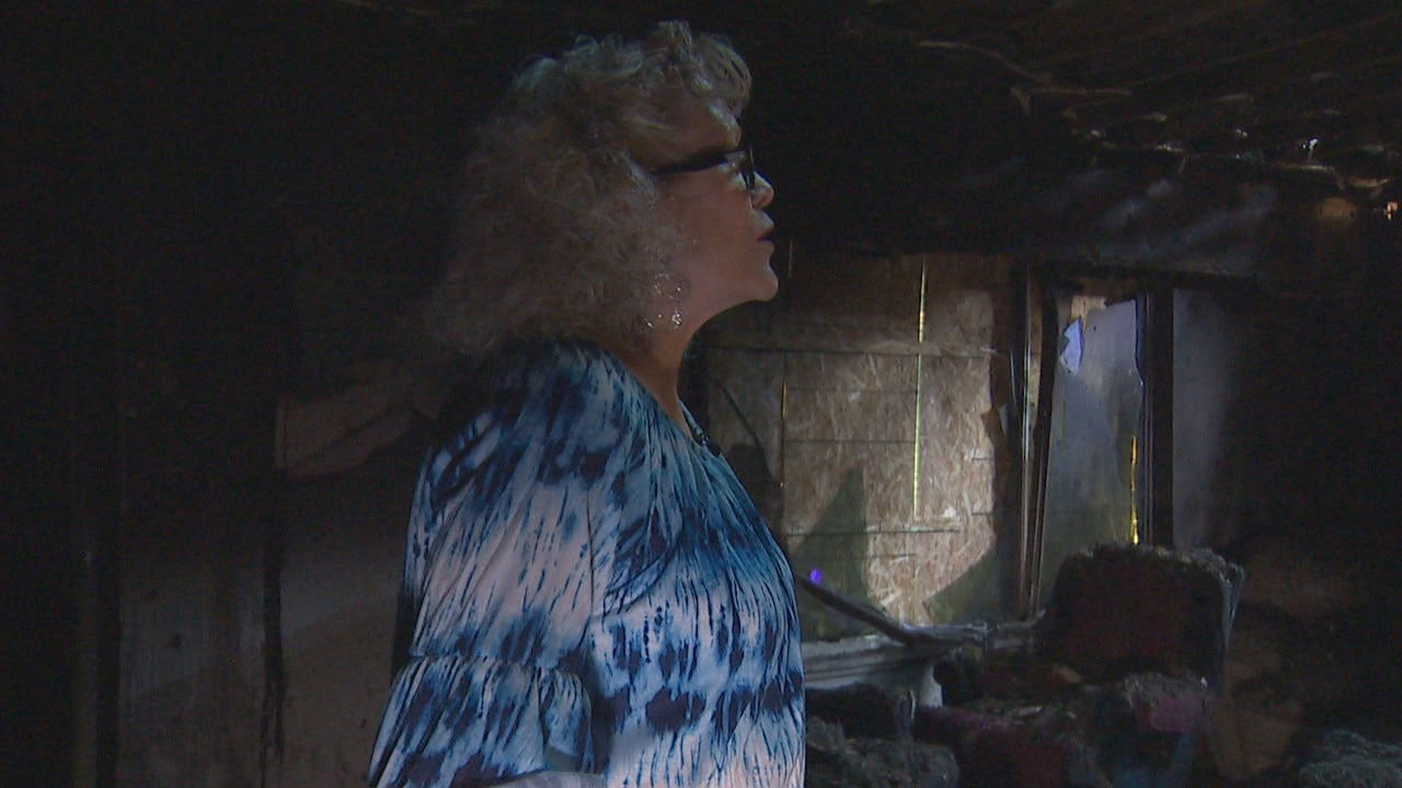 Cathy Kennedy shows where the fire destroyed part of her home and killed her husband and two dogs. (KOMO Photo)