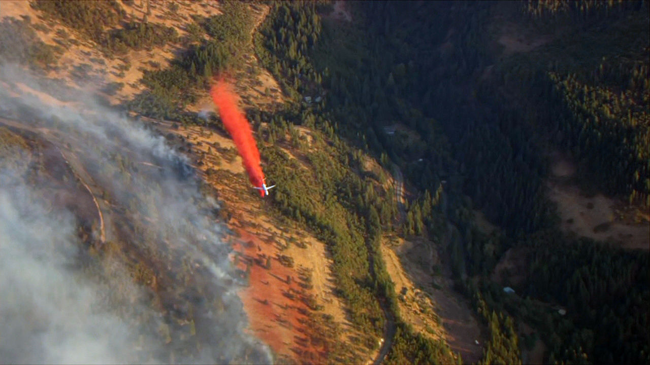 An air tanker drops fire retardant while fighting a 50-acre fire burning in the Columbia River Gorge near Mosier, Oregon on Wednesday evening, Aug. 12, 2020. (KATU/Chopper 2)