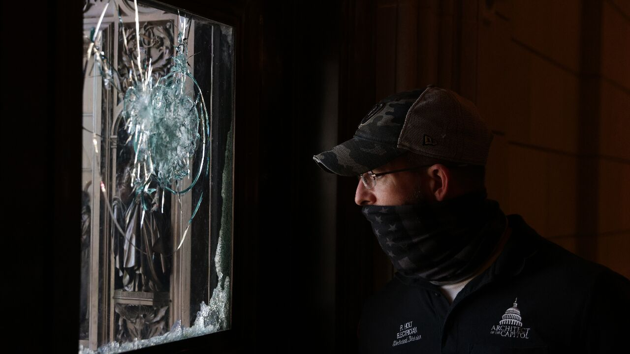 A member of the Architect of the Capitol inspects a damaged entrance of the U.S.{ }Photo by Alex Wong/Getty Images)