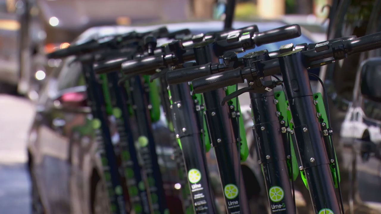 Rentable e-scooters are lined up on a Portland sidewalk - KATU image.jpg