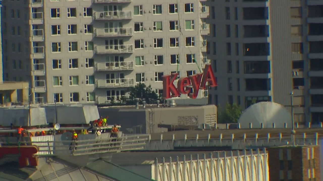 A helicopter removes the iconic KeyArena sign from the future Climate Pledge Arena (KOMO Photo)