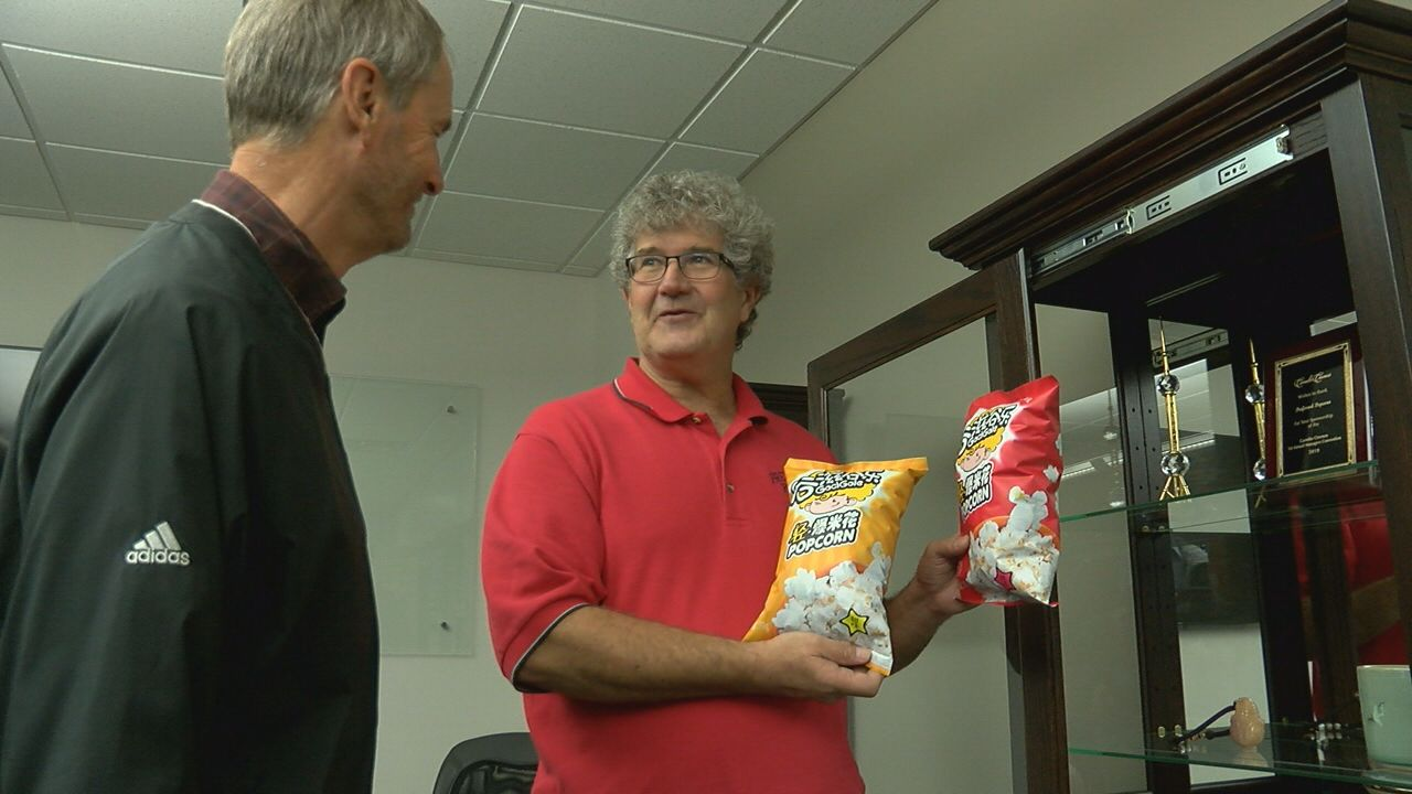 Daryl Hunnicutt and Norm Krug of Preferred Popcorn look at the new Chinese packages of the popcorn they grow. (NTV News)