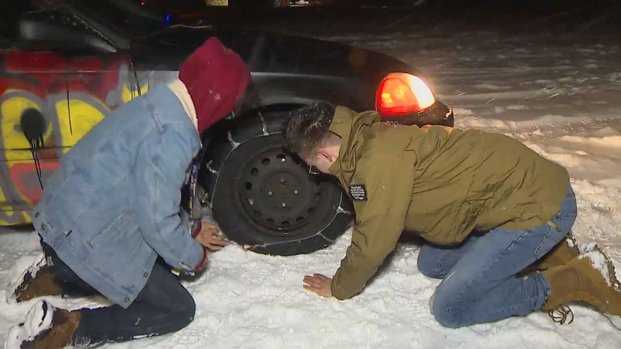 Travelers put on tire chains as they go over Stevens Pass amid heavy snow 12-11-19. (KOMO News)