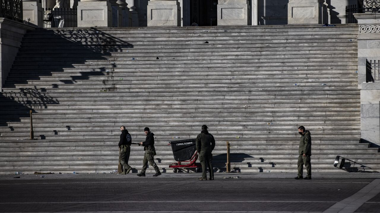 Police officers survey the damage and debris left on the Eastern steps.{ }Photo by Alex Wong/Getty Images)