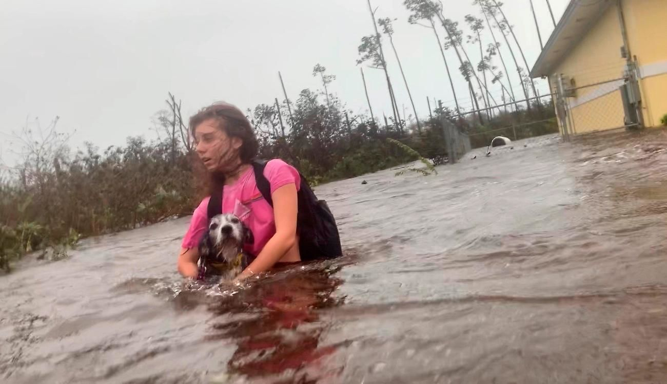 Julia Aylen wades through waist deep water carrying her pet dog as she is rescued from her flooded home during Hurricane Dorian in Freeport, Bahamas, Tuesday, Sept. 3, 2019. (AP Photo/Tim Aylen)
