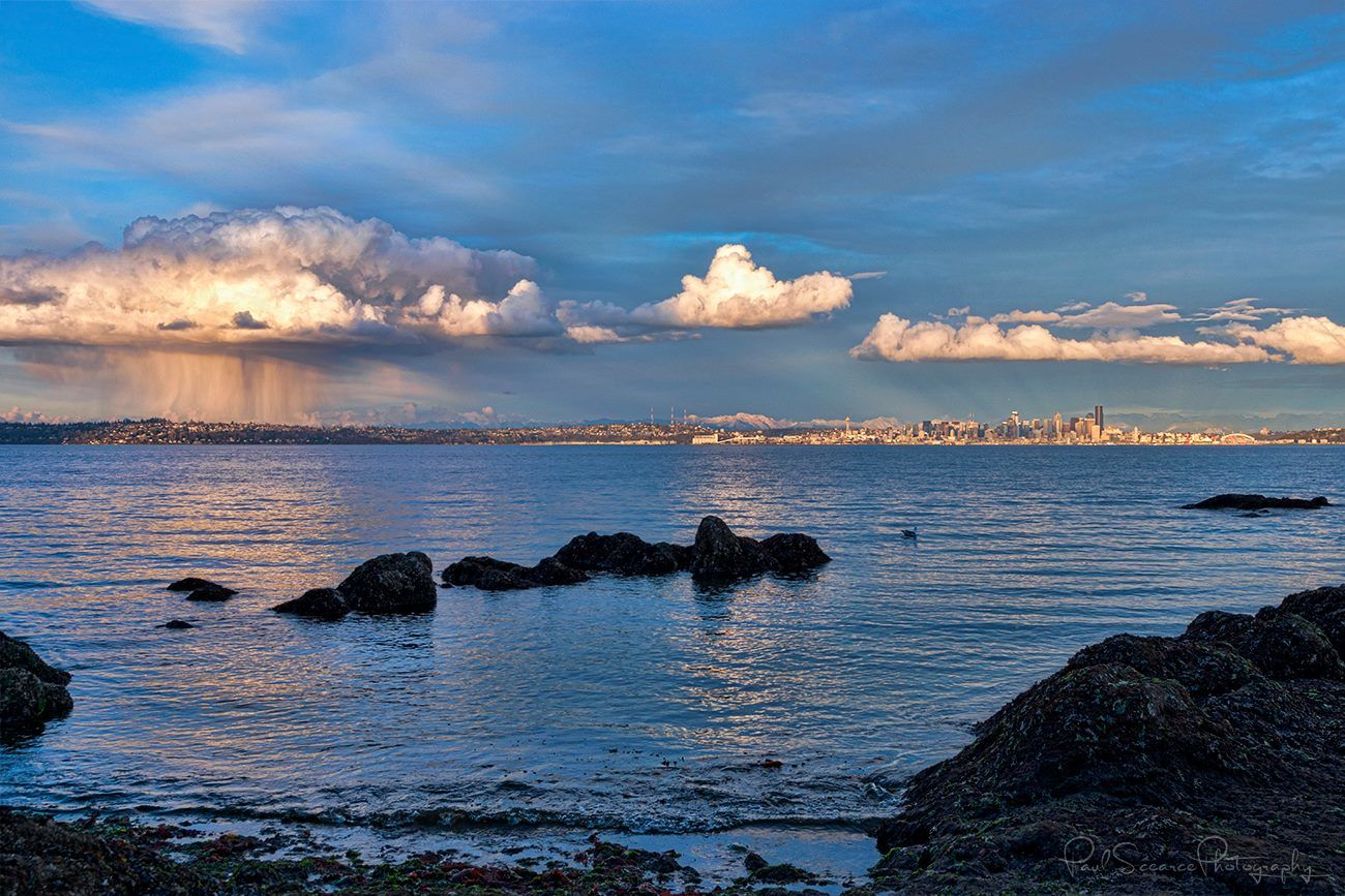 A rain shower falls over North Seattle as anti-crepuscular rays shine behind the city's Skyline on March 24, 2018 (Photo: Paul Scearce)