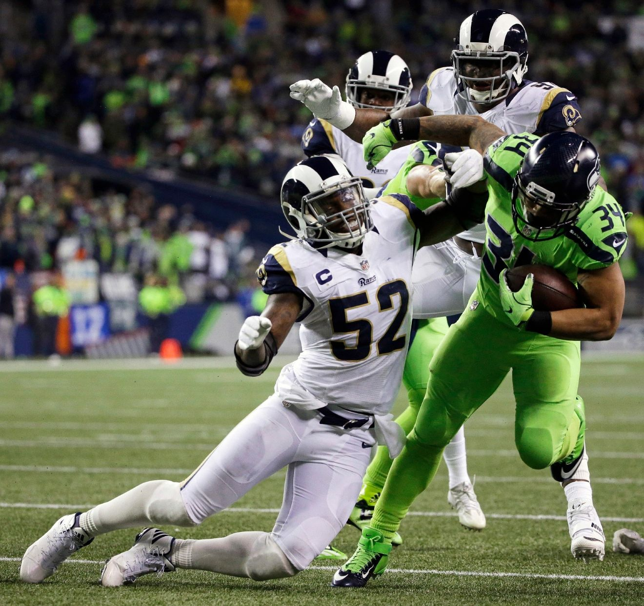 Seattle Seahawks running back Thomas Rawls (34) pushes off Los Angeles Rams middle linebacker Alec Ogletree (52) in the second half of an NFL football game, Thursday, Dec. 15, 2016, in Seattle. (AP Photo/Elaine Thompson)