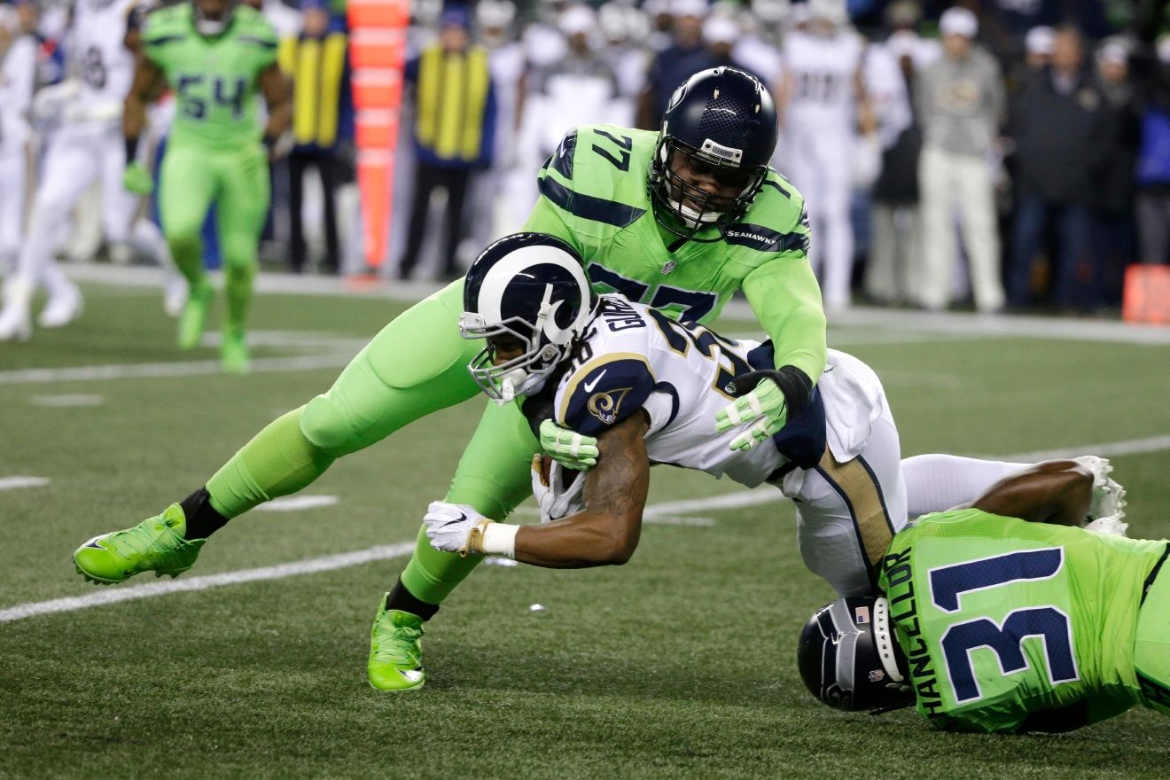 Los Angeles Rams running back Todd Gurley (30) is tackled by Seattle Seahawks defensive tackle Ahtyba Rubin (77) and strong safety Kam Chancellor (31) in the first half of an NFL football game, Thursday, Dec. 15, 2016, in Seattle. (AP Photo/Elaine Thompson)