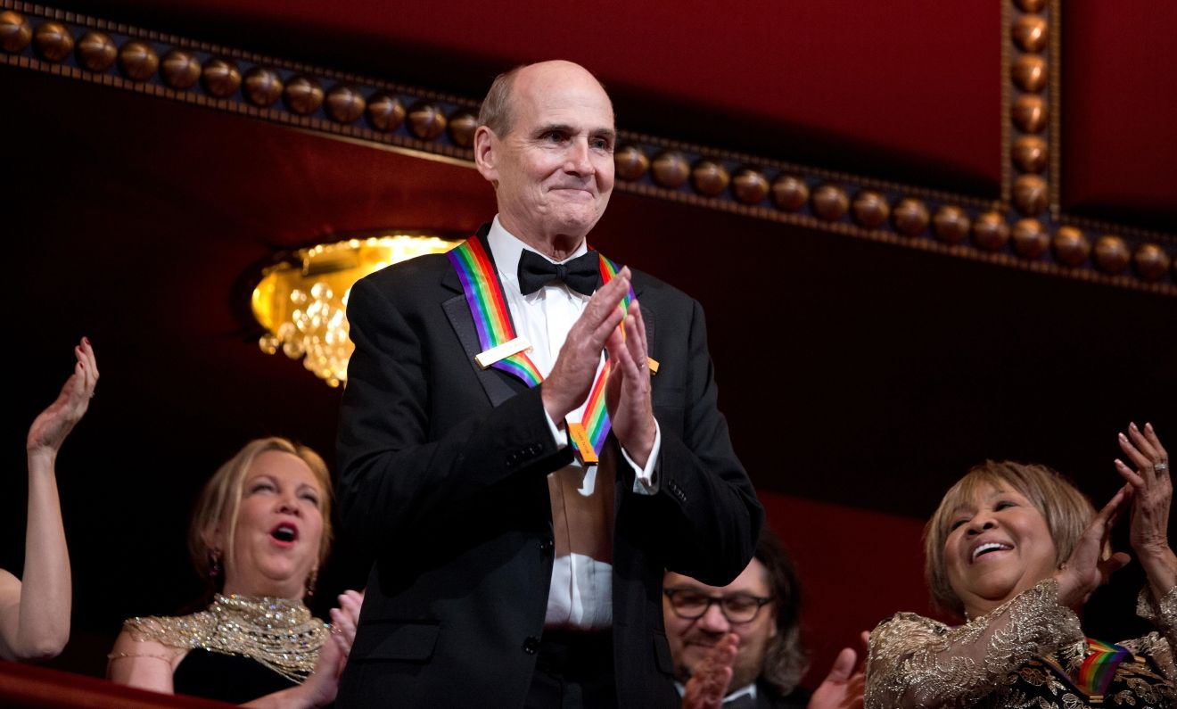 Recipient of the 2016 Kennedy Center Honor award, musician James Taylor, acknowledges the applause during the Kennedy Center Honors gala at the Kennedy Center in Washington, Sunday, Dec. 4, 2016. On the right is honoree gospel and blues singer Mavis Staples. (AP Photo/Manuel Balce Ceneta)