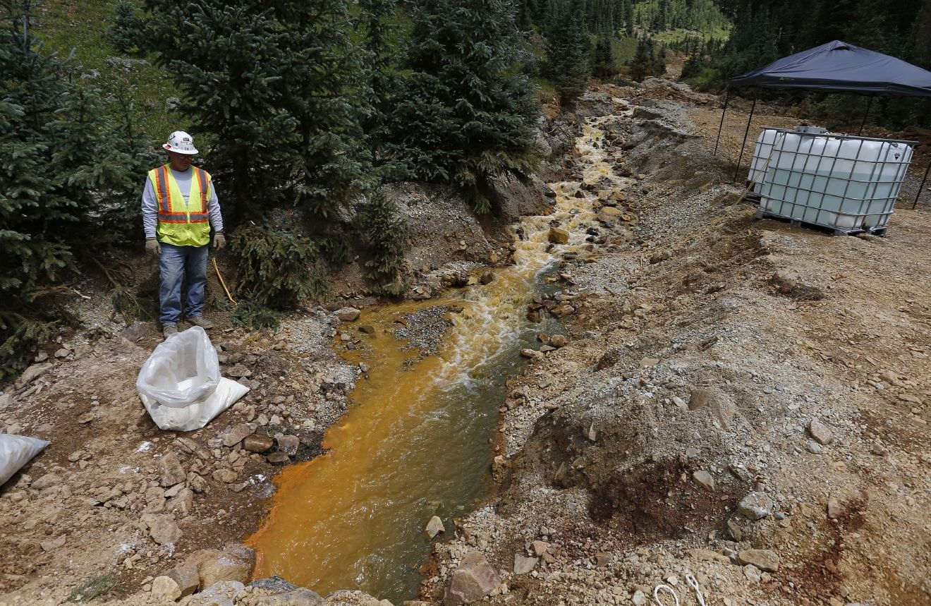 An Environmental Protection Agency contractor works on the clean up in the aftermath of the blowout at the Gold King mine, which triggered a major spill of toxic wastewater, outside Silverton, Colo., Wednesday, Aug. 12, 2015. The head of the Environmental Protection Agency has ordered agency offices nationwide to stop field investigation work for mine cleanups while they reassess the work to ensure there's no potential for spills similar to the one in Colorado. EPA Administrator Gina McCarthy announced the change Wednesday on a visit to Durango, Colo. (AP Photo/Brennan Linsley)