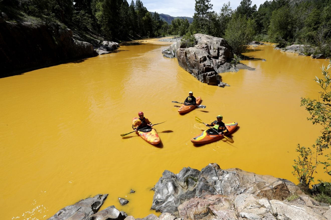 FILE - In this Aug. 6, 2015 file photo, people kayak in the Animas River near Durango, Colo., in water colored from a mine waste spill. New Mexico officials said Thursday, Jan. 14, 2016 that they plan to sue the federal government and the owners of two Colorado mines that were the source of a massive spill last year that contaminated rivers in three Western states. An EPA cleanup crew accidentally triggered the spill in August at the inactive Gold King mine near Silverton, Colo.(Jerry McBride/The Durango Herald via AP, File)