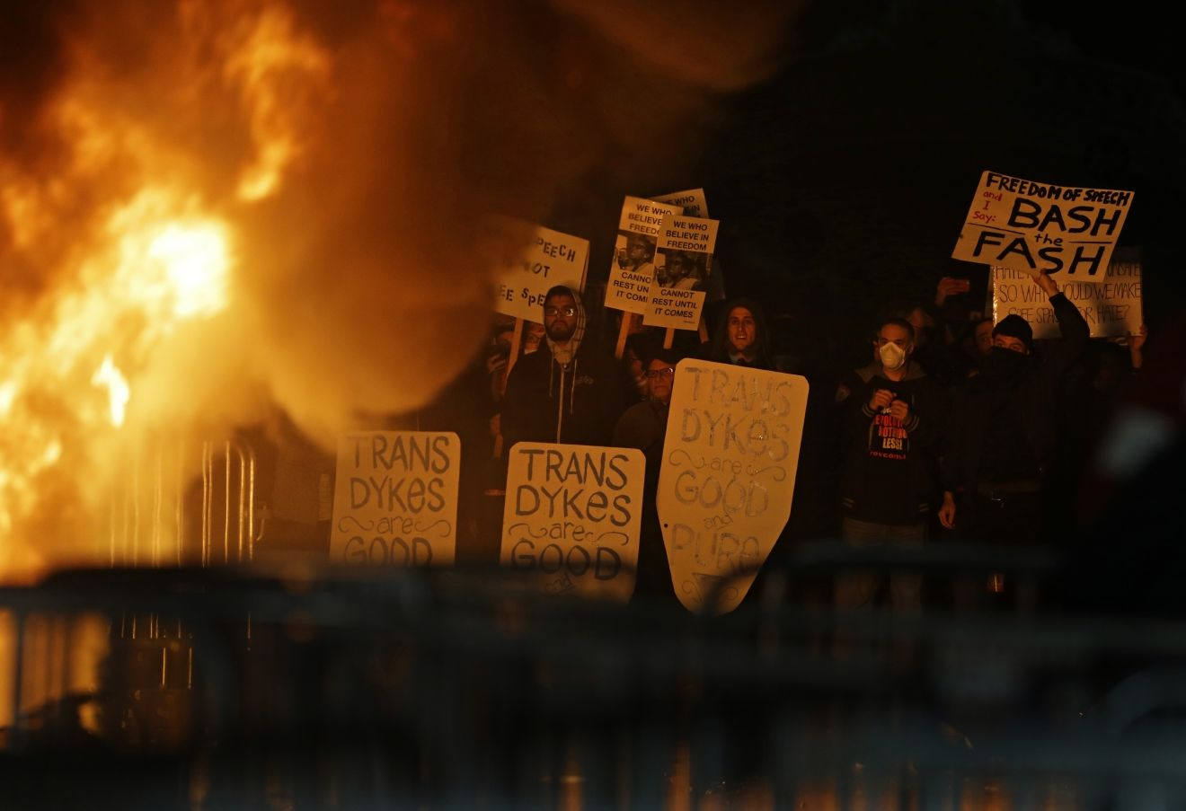 Protestors watch a fire on Sproul Plaza during a rally against the scheduled speaking appearance by Breitbart News editor Milo Yiannopoulos on the University of California at Berkeley campus on Wednesday, Feb. 1, 2017, in Berkeley, Calif. (AP Photo/Ben Margot)