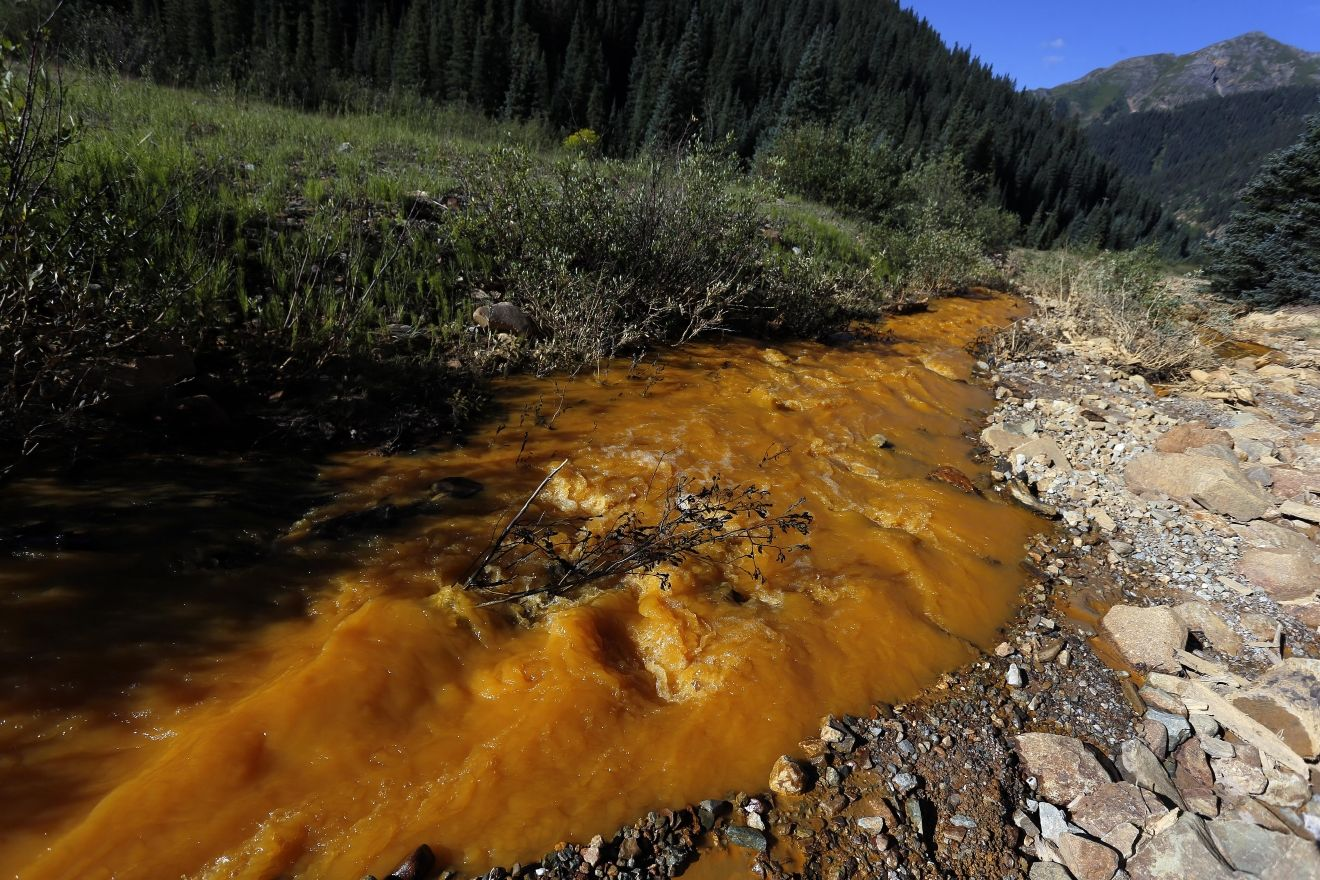 Water flows down Cement Creek just below the site of the blowout at the Gold King mine which triggered a major spill of toxic wastewater, outside Silverton, Colo., Thursday, Aug. 13, 2015. It will take years, if not decades, and many millions of dollars to clean up and manage the toxic wastewater from a this Colorado mine that unleashed a 100-mile-long torrent of heavy metals, affecting the livelihoods of residents in three states, according to some experts. (AP Photo/Brennan Linsley)