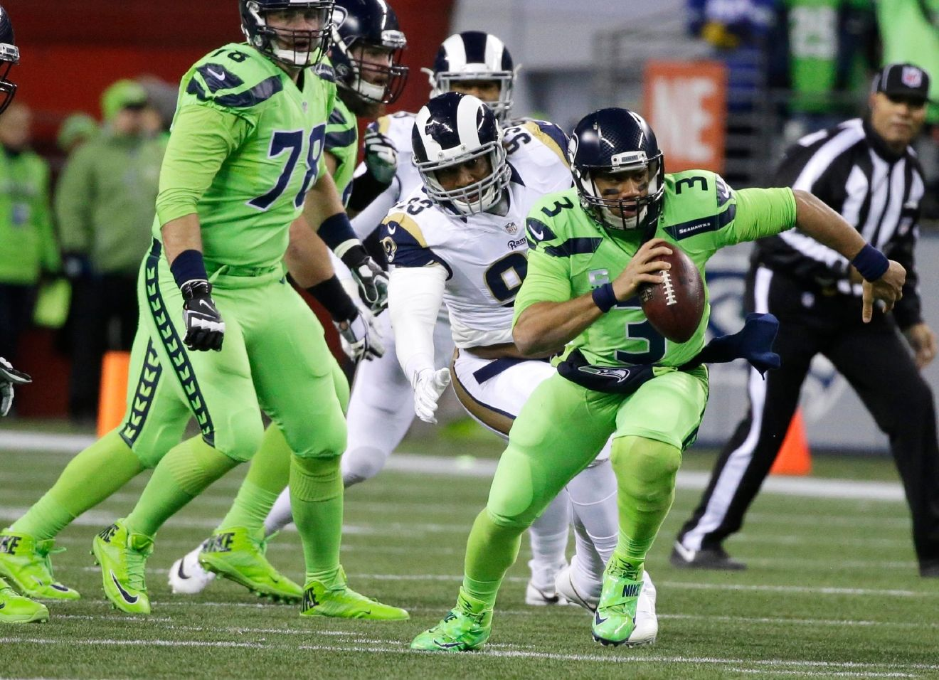 Seattle Seahawks quarterback Russell Wilson (3) scrambles away from Los Angeles Rams defensive end Ethan Westbrooks, center, in the first half of an NFL football game, Thursday, Dec. 15, 2016, in Seattle. (AP Photo/Elaine Thompson)