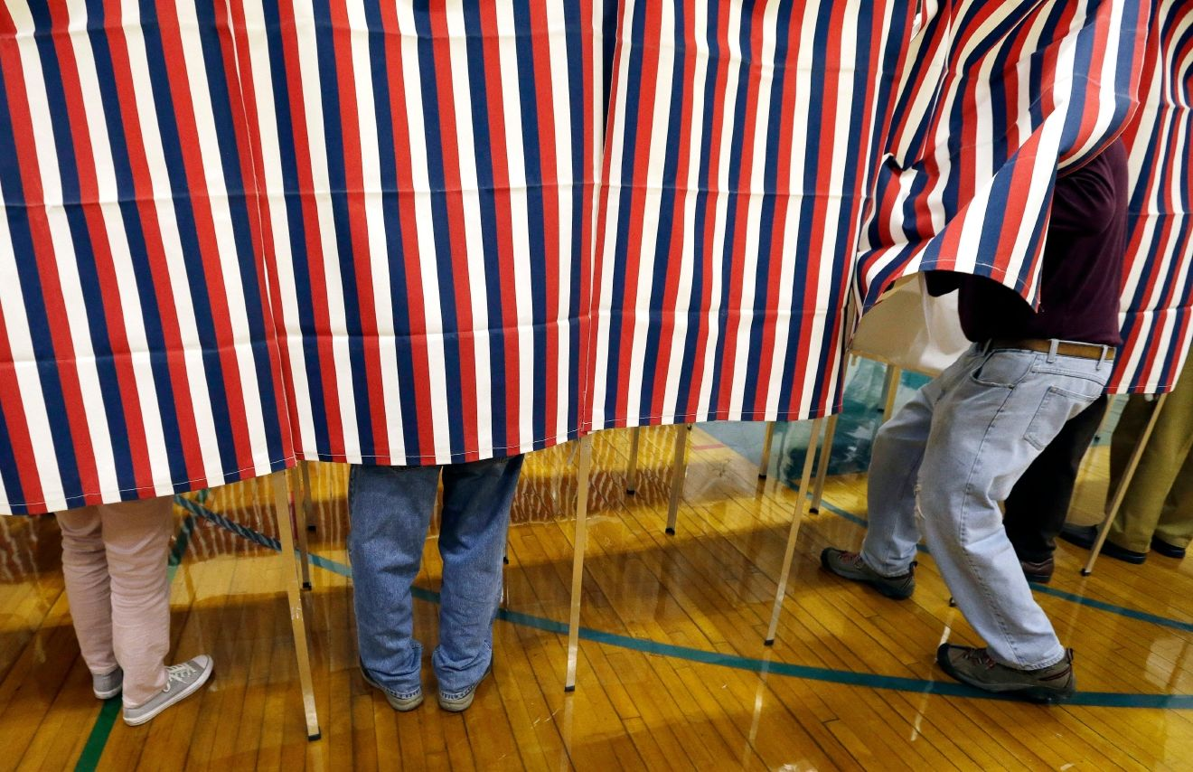 FILE - In this Nov. 8, 2016 file photo, a voter enters a booth at a polling place in Exeter, N.H. (AP Photo/Elise Amendola, File)
