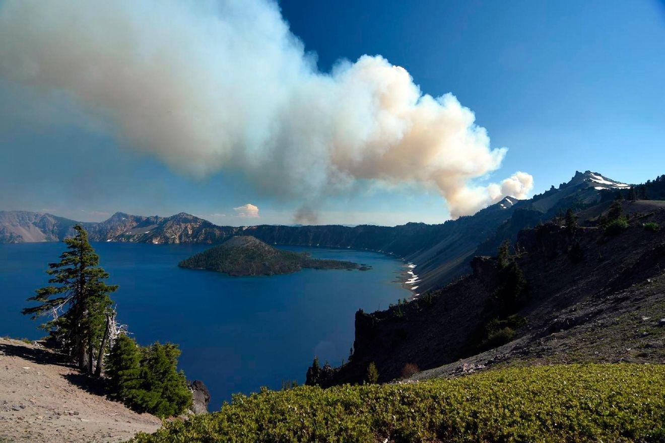 This photo provided by Inciweb.gov, shows smoke from Bybee Creek Wildfire drifting over Crater Lake, Ore., July 30, 2016. The wildfire burning west of Crater Lake National Park has grown to more than 400 acres as of Tuesday, and the park remains open, but fire officials say West Rim Drive could be intermittently closed over the next couple of days. (Cheryl Chipman/Inciweb.gov)