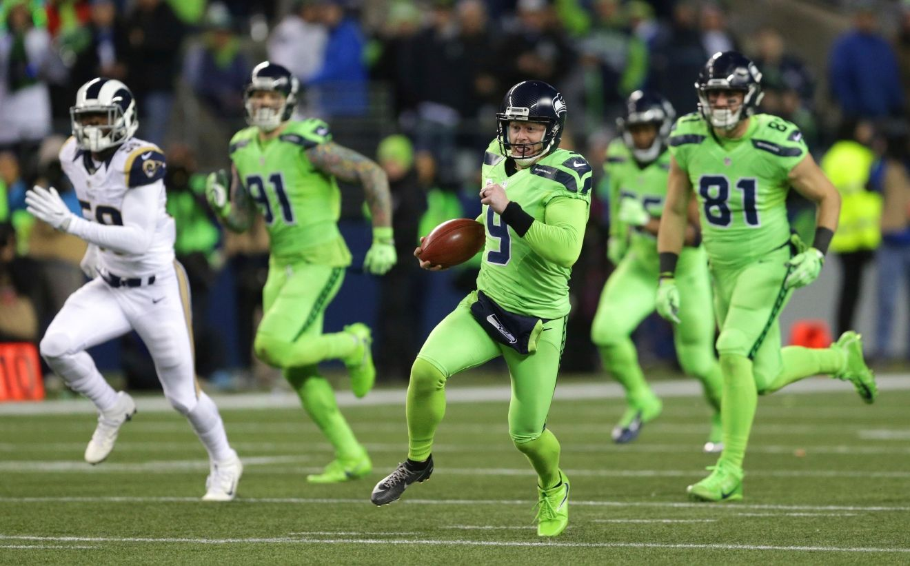 Seattle Seahawks punter Jon Ryan (9) runs the ball after a fake punt against the Los Angeles Rams in the second half of an NFL football game, Thursday, Dec. 15, 2016, in Seattle. Ryan suffered an injury on the play and left the game. (AP Photo/Scott Eklund)