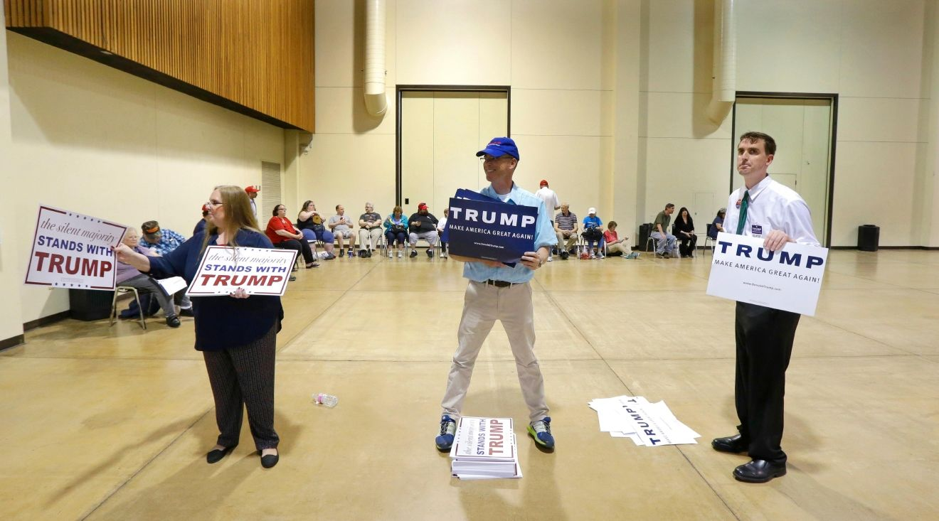 Volunteers hand out signs before a the start of a rally for Republican presidential candidate Donald Trump in Eugene, Ore., Friday, May 6, 2016. (AP Photo/Ted S. Warren)