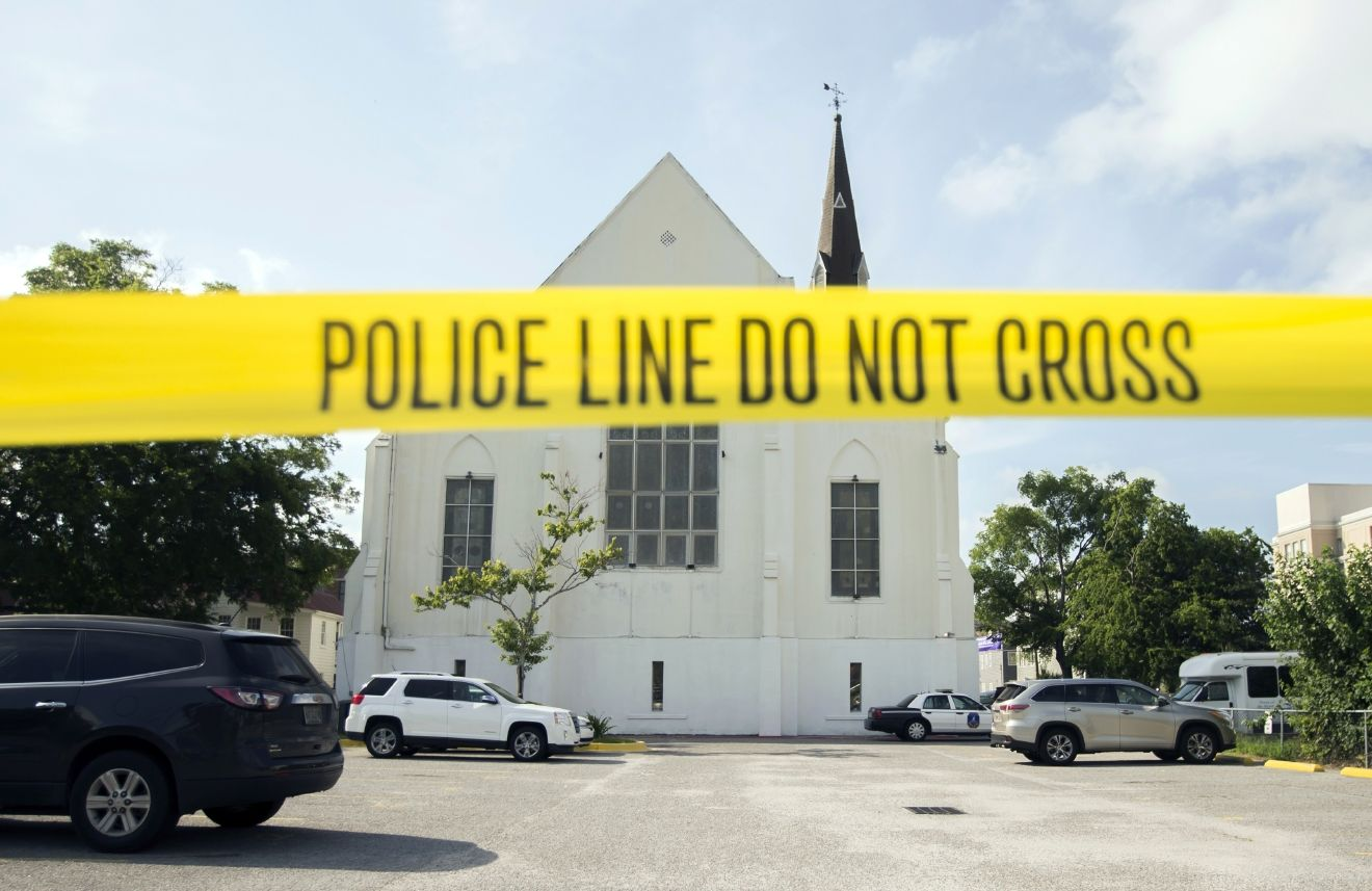 FILE - In this June 19, 2015 file photo, police tape surrounds the parking lot behind the AME Emanuel Church as FBI forensic experts work the crime scene, in Charleston, S.C. Attorneys for the man charged with killing nine people at a Charleston church are challenging federal prosecutors' intention to seek the death penalty against him. Lawyers for Dylann Roof argue in a motion filed Monday, Aug. 1, 2016, that the death penalty and federal death penalty law are unconstitutional.  (AP Photo/Stephen B. Morton, File)