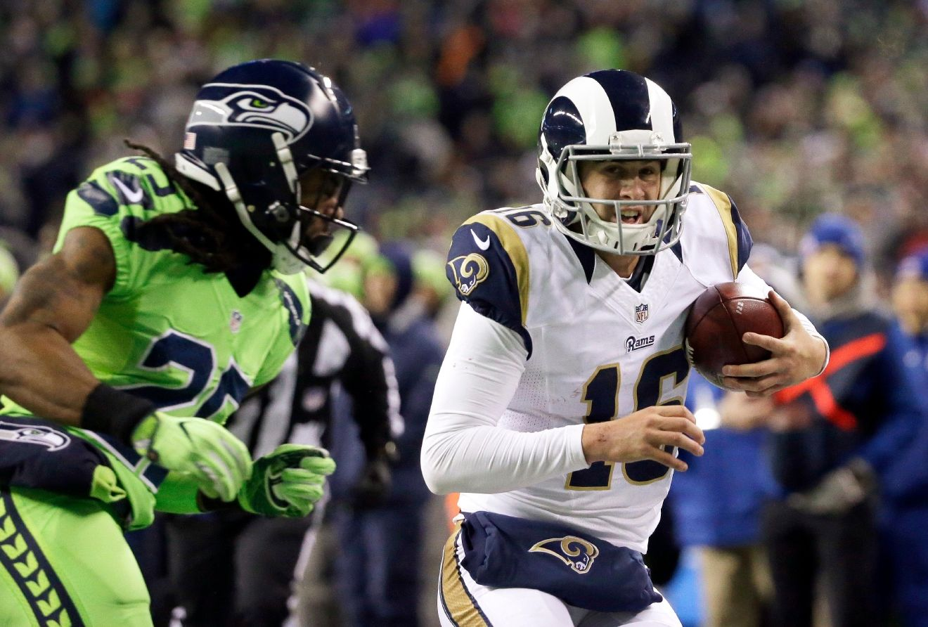 Los Angeles Rams quarterback Jared Goff, right, heads for the sideline just before being hit by Seattle Seahawks cornerback Richard Sherman, left, in the second half of an NFL football game, Thursday, Dec. 15, 2016, in Seattle. Goff left the field with an injury after the play. (AP Photo/Elaine Thompson)