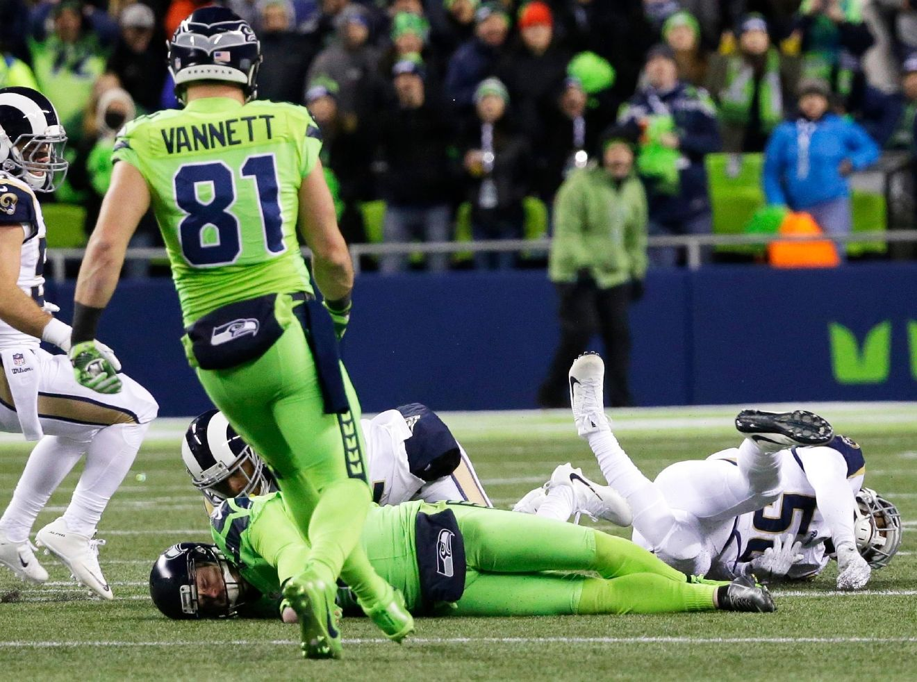 Seattle Seahawks punter Jon Ryan, lower left, lies on the turf after taking a hard hit while running the ball on a fake punt play against the Los Angeles Rams in the second half of an NFL football game, Thursday, Dec. 15, 2016, in Seattle. Ryan left the game with an injury on the play. (AP Photo/Elaine Thompson)