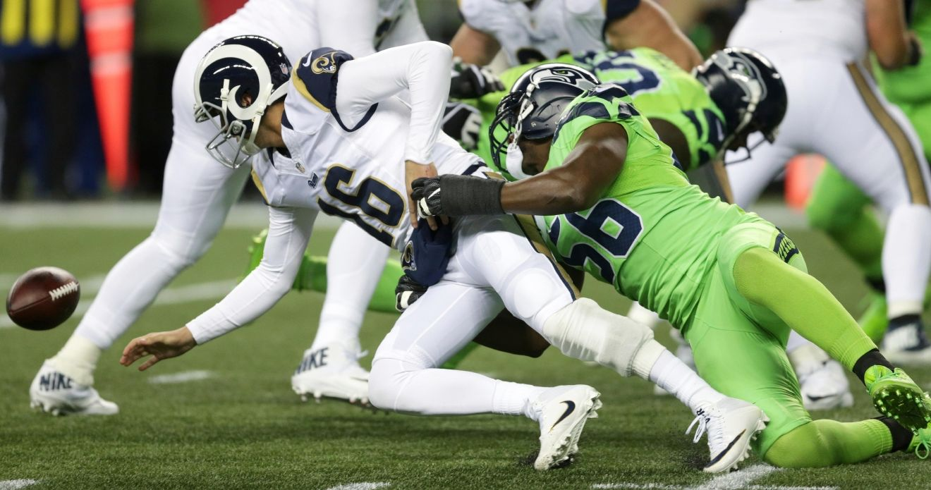 Los Angeles Rams quarterback Jared Goff (16) fumbles as he is tackled by Seattle Seahawks defensive end Cliff Avril (56) in the second half of an NFL football game, Thursday, Dec. 15, 2016, in Seattle. Goff recovered the ball. (AP Photo/Scott Eklund)