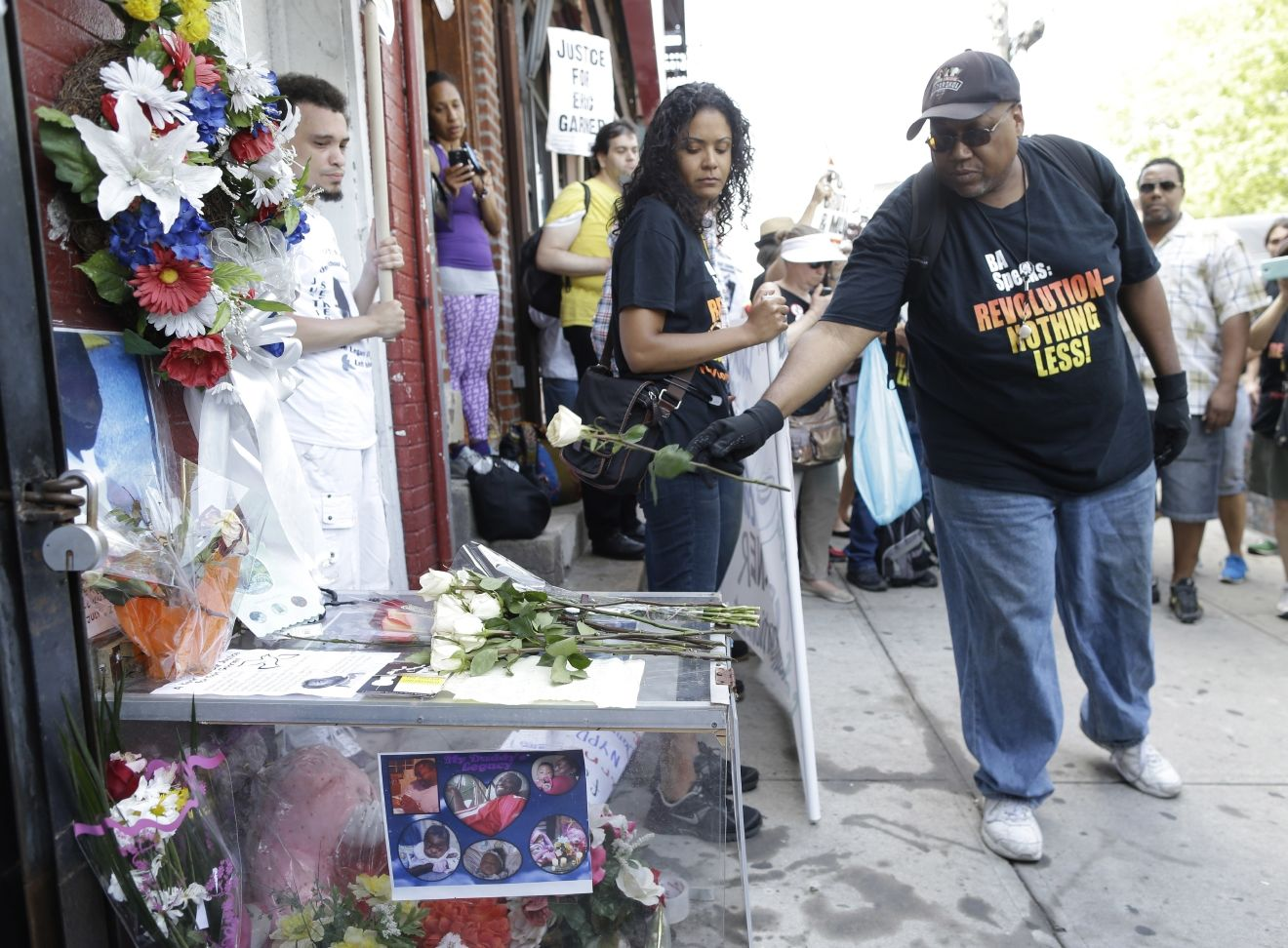FILE - In this July 17, 2015 file photo, a man places a rose on a memorial for Eric Garner during a rally at the site of his fatal encounter with police in the Staten Island borough of New York. (AP Photo/Mary Altaffer, File)