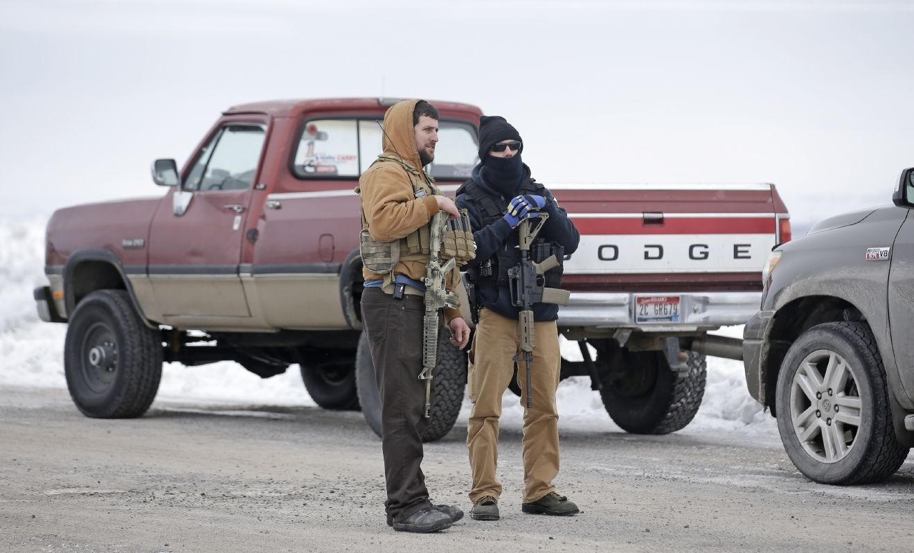 "FILE - In this Jan. 9, 2016 file photo, men stand guard after members of the ""3% of Idaho"" group and several other organizations arrived at the Malheur National Wildlife Refuge, near Burns, Ore. The contrasting actions of two rural Oregon sheriffs during the recent armed standoff at the refuge were striking: one worked with federal officials to end the siege while another questioned the FBIÂ?s authority and offered words of support for the ragtag group that seized property in the stateÂ?s high desert country. (AP Photo/Rick Bowmer, File)"