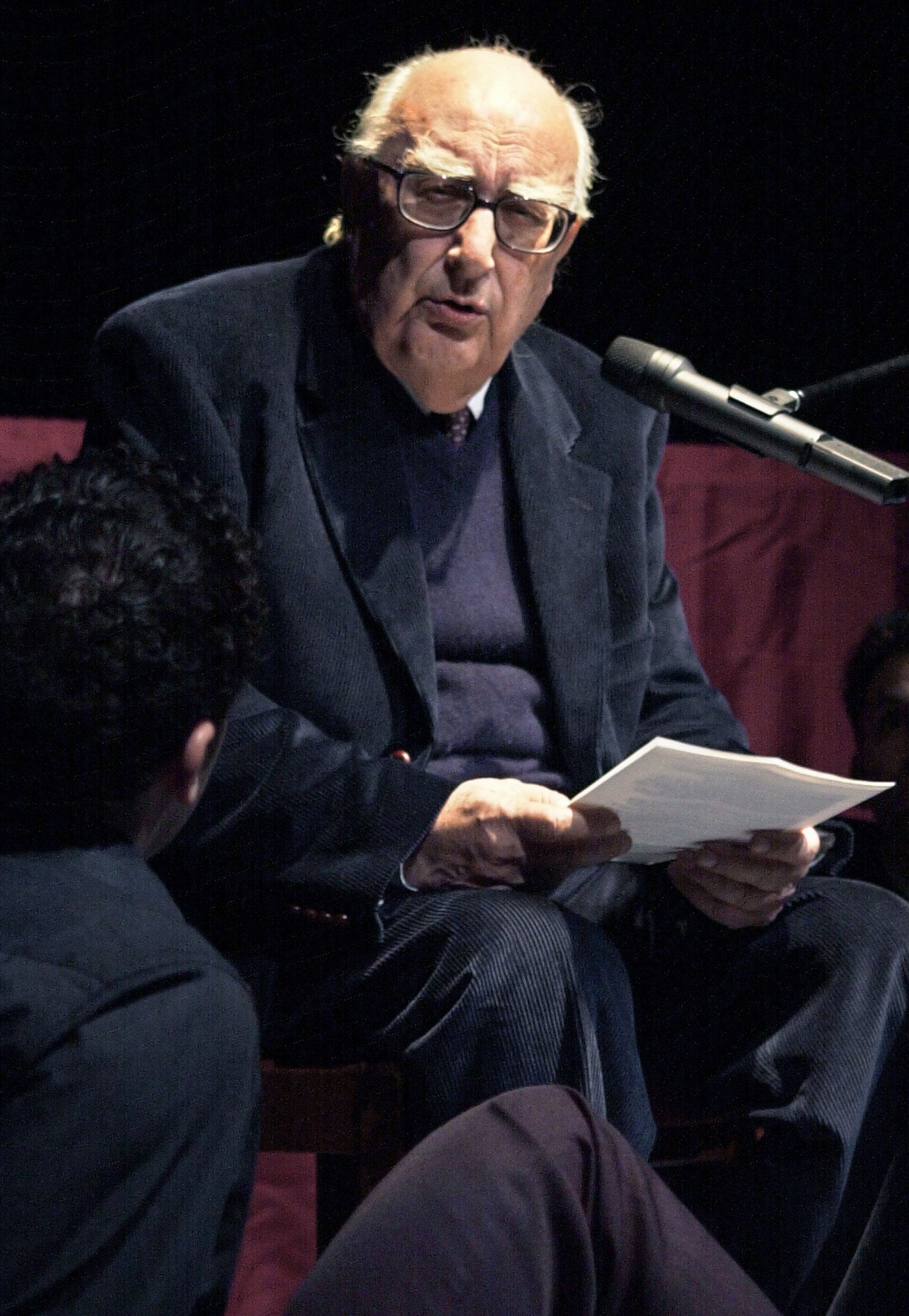 FILE - In this March 5, 2001 file photo, Italian author Andrea Camilleri reads a Luigi Priandello novel at Rome's Piccolo Eliseo theater.{ } (AP Photo/Gregorio Borgia, File)