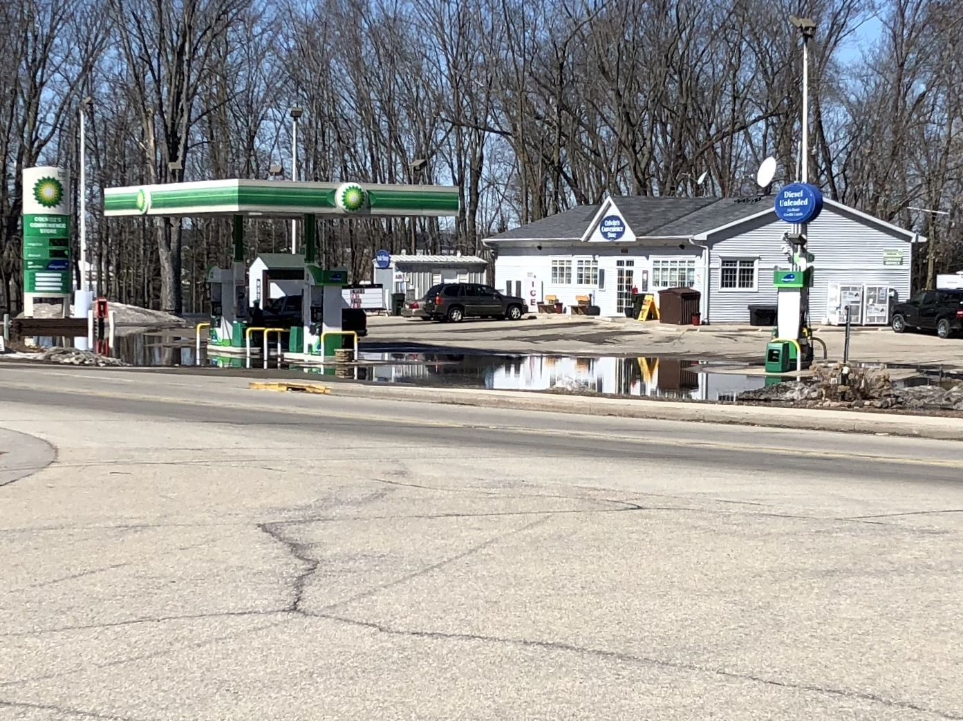 Flood waters settle in low spots of the parking lot of a gas station on Hwy. 54 in Shiocton March 22, 2019. (WLUK/Eric Peterson)