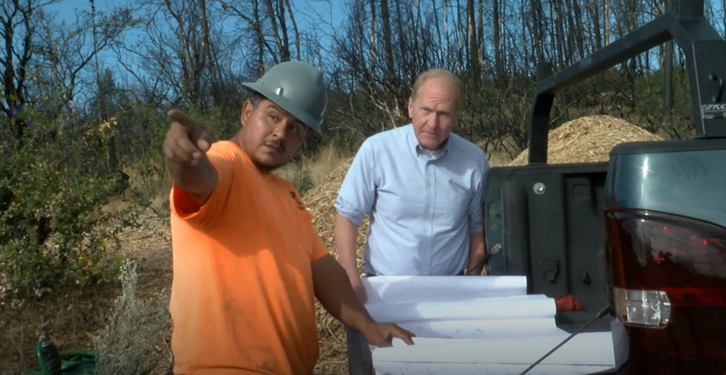 Project Foreman, Nacho Aguila, showing Mike the plans for this site's construction. (KRCR)