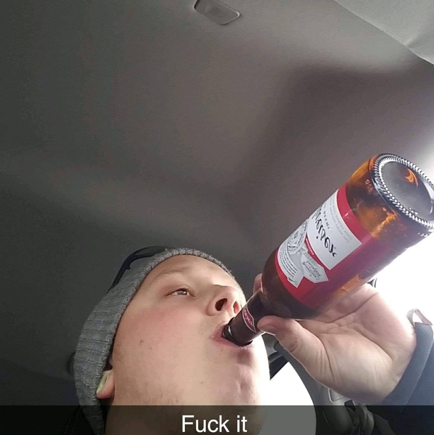 Photo of Keigan Matthew Sumsion apparently drinking a beer while in the driver's seat of his car.