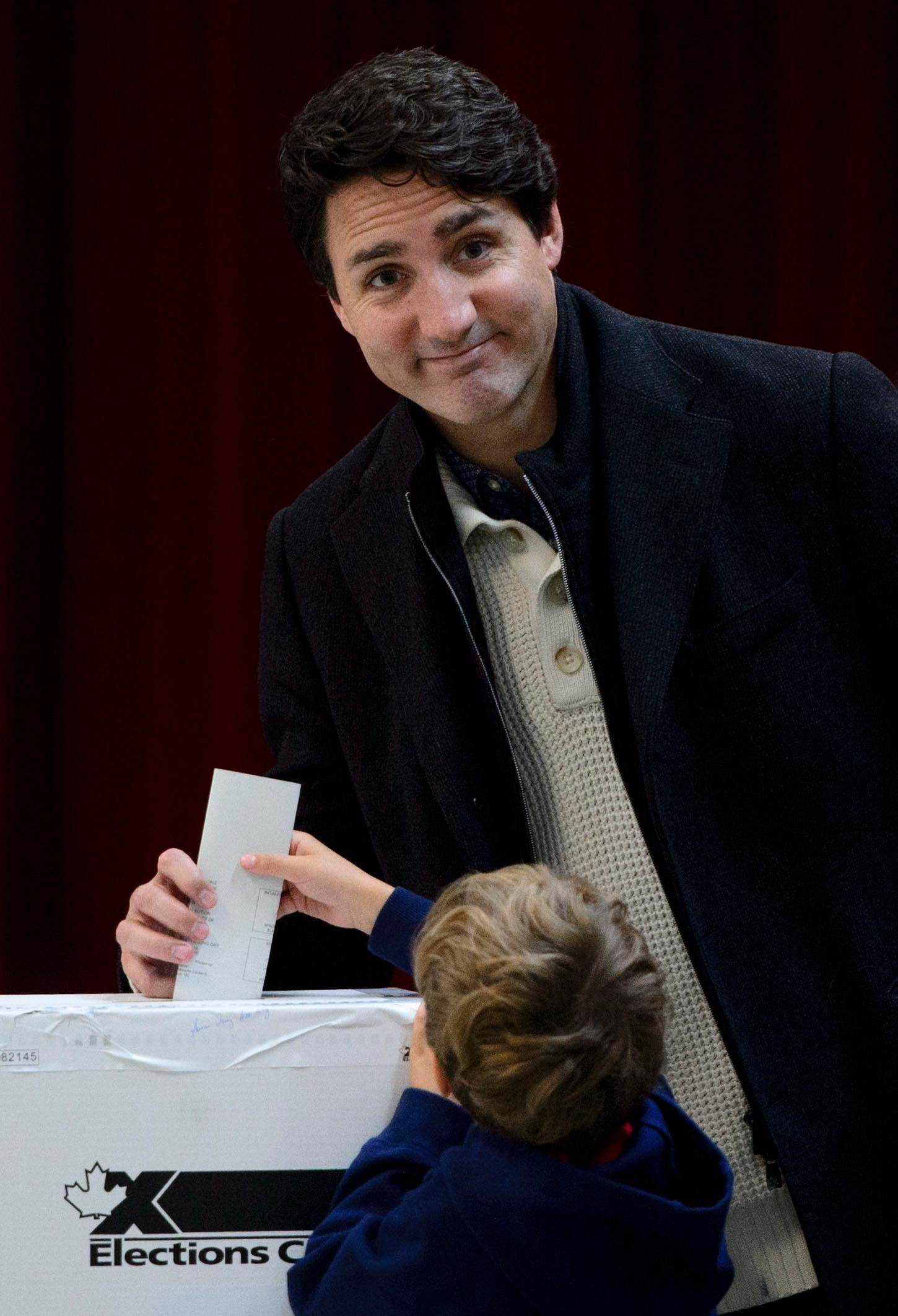 Hadrien helps his dad, Canadian Prime Minister and Liberal Leader Justin Trudeau, cast his ballot in Montreal, Monday, Oct. 21, 2019. Trudeau faced the threat of being knocked from power after one term as the nation held parliamentary elections on Monday. (Sean Kilpatrick/The Canadian Press via AP)