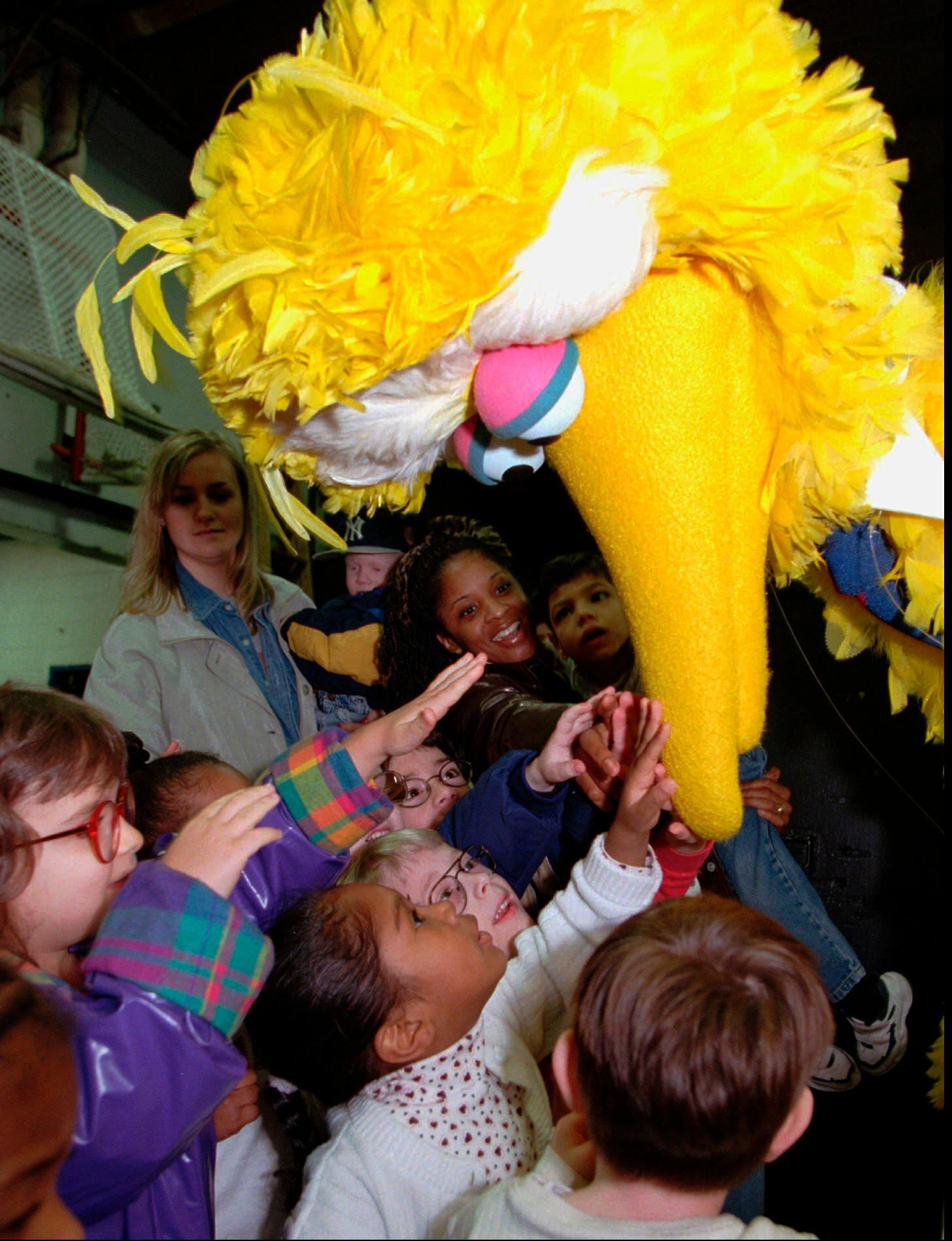 FILE - In this March 20, 1998, file photo, students from the Overbrook School for the Blind reach up and touch the beak of Sesame Street's Big Bird character before his performance in Philadelphia.{ } (AP Photo/Chris Gardner, File)